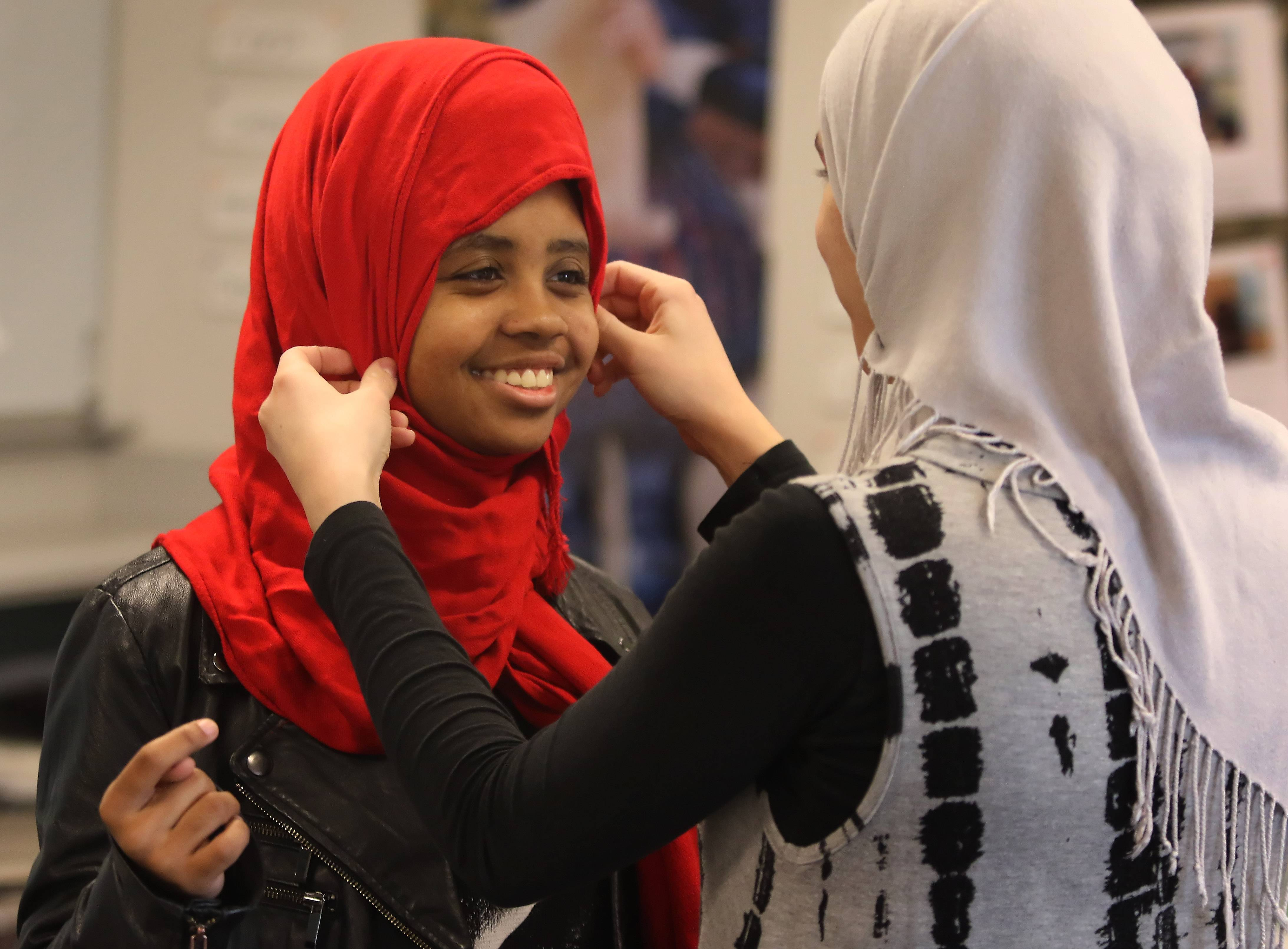 "Vernon Hills High School senior Yasmeen Abdallah, who is Muslim, helps junior Charli Mosley, left, put on a hijab during the ""Walk a Mile in Her Hijab"" event Wednesday at the school."