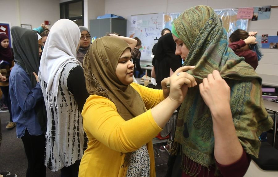 "Vernon Hills High School senior Hiba Hashim, in yellow, helps senior Carter Ray with her hijab during the ""Walk a Mile in Her Hijab"" event Wednesday at the school. Hashim, who is Muslim, is president of the school's Muslim Student Association that organized the event to promote awareness of the Muslim faith."