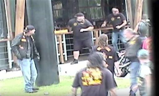 In this image made from Texas Department of Public Safety video, bikers run for cover as a shooting erupts outside a Twin Peaks restaurant in Waco, Texas, on May 17, 2015. The latest trove of potential grand jury evidence reviewed by the AP depicts a chaotic, bloody scene in which police swarmed into the shootout between rival biker gangs that left about 20 wounded and arrested nearly 200 people. Four of the nine people killed in the melee were struck with bullets from the same caliber rifles fired by Waco police, according to the evidence, which provides the most insight yet into what role authorities may have played in the deaths. (Texas Department of Public Safety via AP)