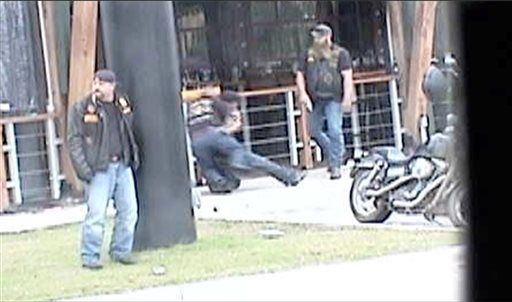 In this image made from Texas Department of Public Safety video, two bikers wrestle as another, right, walks up to them after a shooting erupts outside a Twin Peaks restaurant in Waco, Texas, on May 17, 2015. The latest trove of potential grand jury evidence reviewed by the AP depicts a chaotic, bloody scene in which police swarmed into the shootout between rival biker gangs that left about 20 wounded and arrested nearly 200 people. (Texas Department of Public Safety via AP)