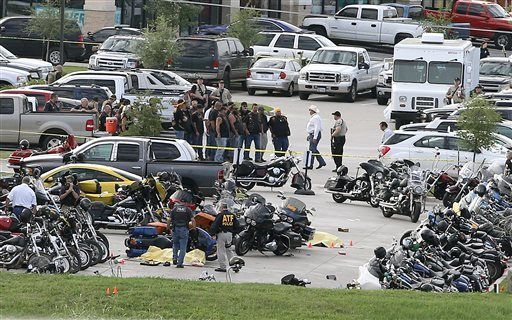 FILE - In this May 17, 2015 file photo, authorities investigate a shooting in the parking lot of the Twin Peaks restaurant, in Waco, Texas.Four of the nine people killed in a melee between rival biker gangs outside a Texas restaurant were struck by the same caliber of rifle fired by Waco police, according to evidence obtained by The Associated Press that provides the most insight yet into whether authorities were responsible for any of the deaths and injuries.