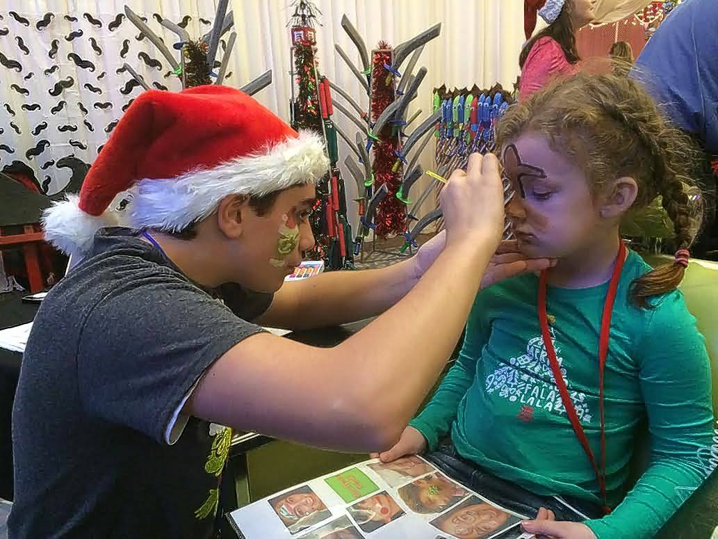 Kendall Atkinson, 7, of Bolingbrook gets her face painted Saturday while receiving medicine through an IV at Operation North Pole in Rosemont.