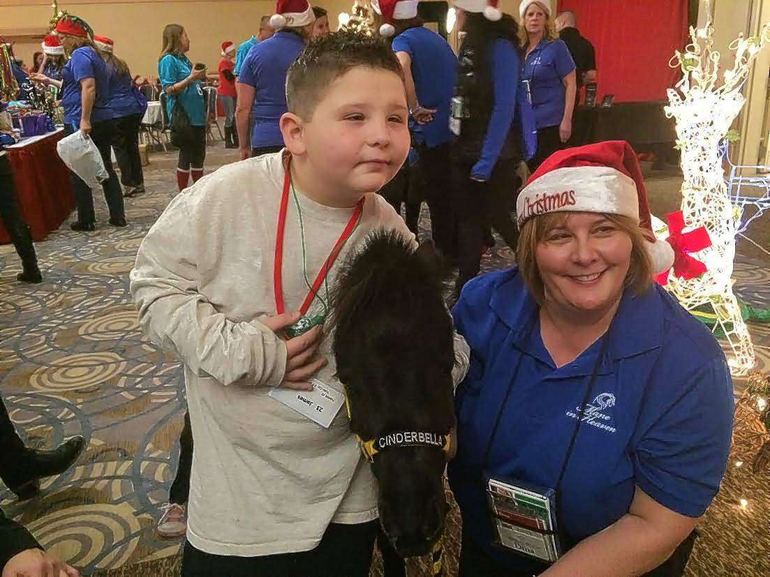 JD Harley of Elburn poses for a photo Saturday with a pony named Cinderella at Operation North Pole in Rosemont.