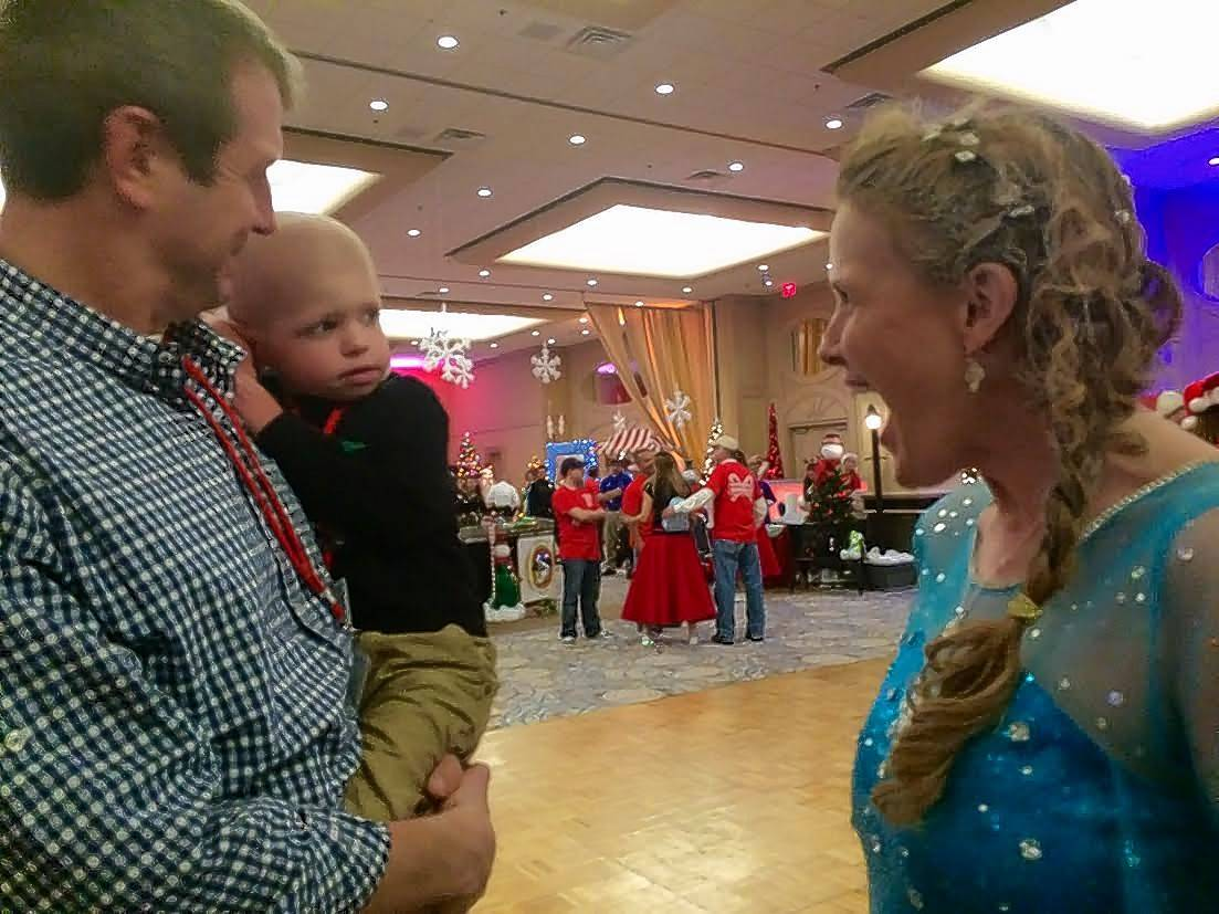 "Park Ridge resident Tim Thompson holds his 3-year-old son, Tommy, while he visits with Elsa from ""Frozen"" on Saturday at Operation North Pole in Rosemont."