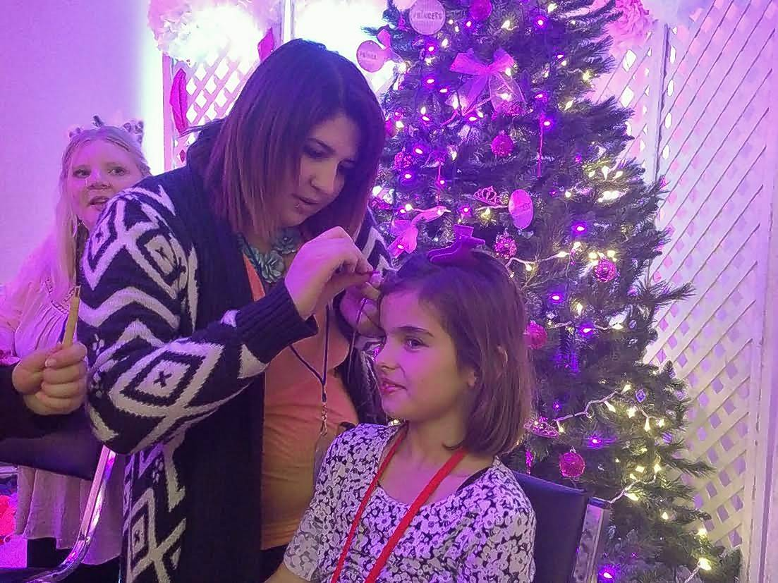 McKinley Parchim, 8, of St. Anne gets her hair done Saturday at a makeover station at Operation North Pole in Rosemont.