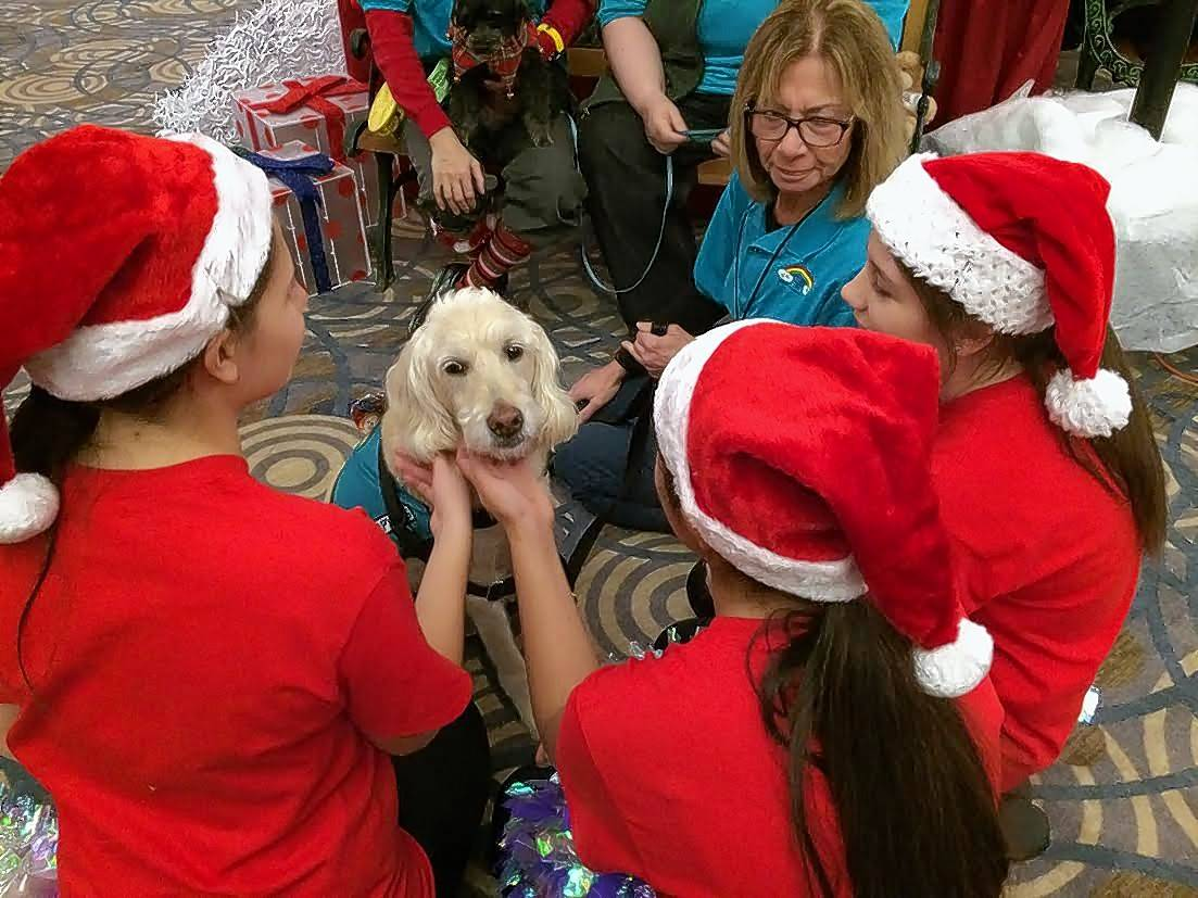 Students from Barrington's Prairie Campus and Station middle schools visit with animals from Rainbow Animal Assisted Therapy before entertaining the crowd Saturday at Operation North Pole in Rosemont.