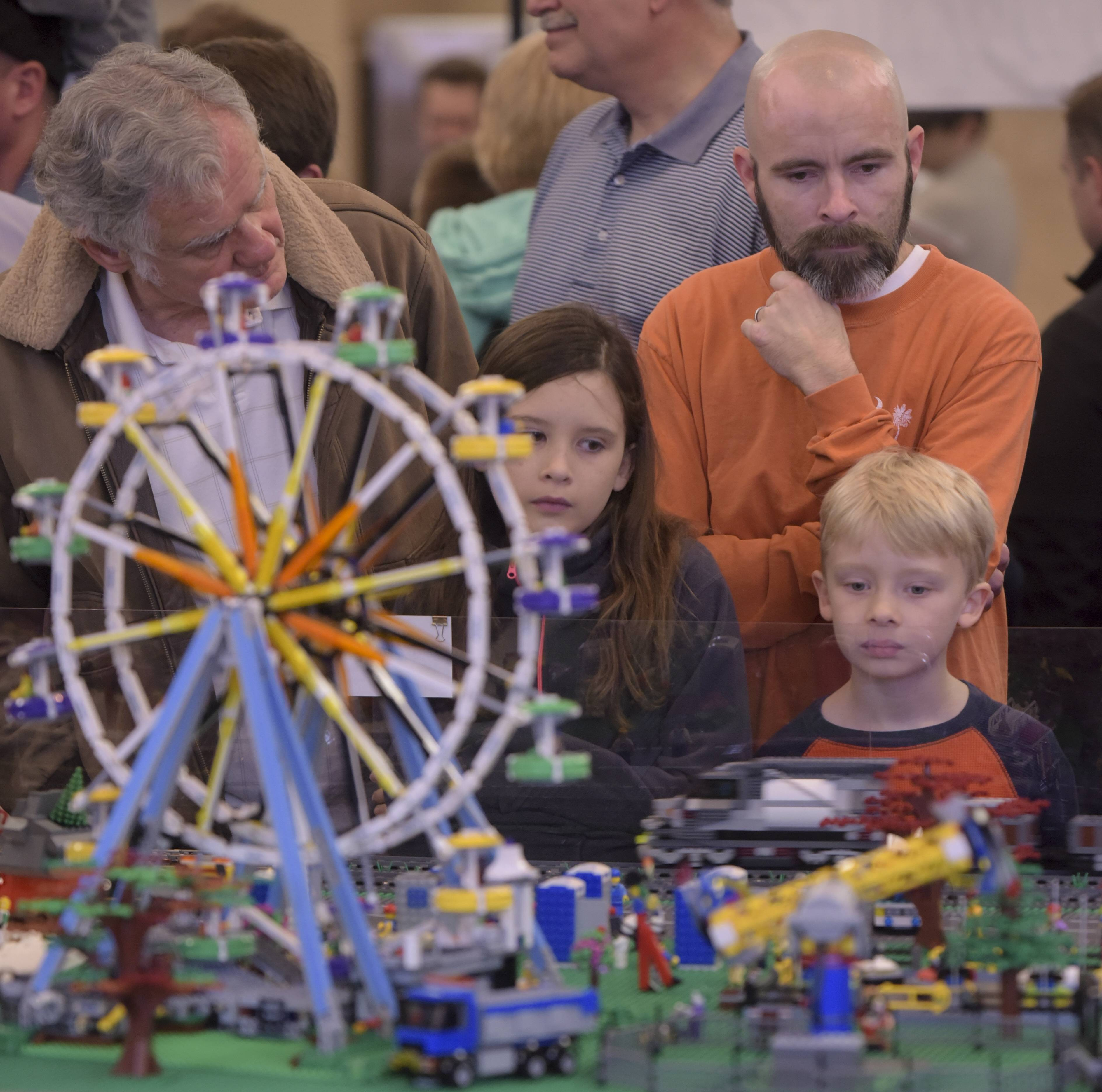 Jeremy Huggin and his children, Grace, 10, and Ben, 7, of Batavia check out a Lego creation Sunday at the 14th annual Lego Train Show at Cantigny Park.