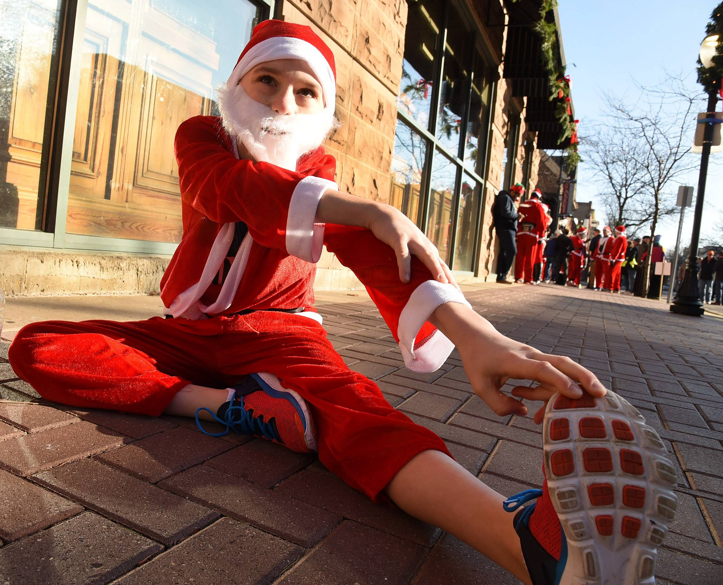 Bob Chwedyk/bchwedyk@dailyherald.com Eleven-year-old Gavin Wright, of Arlington Heights stretches before the start of the annual 5K Santa Run through downtown Arlington Heights.
