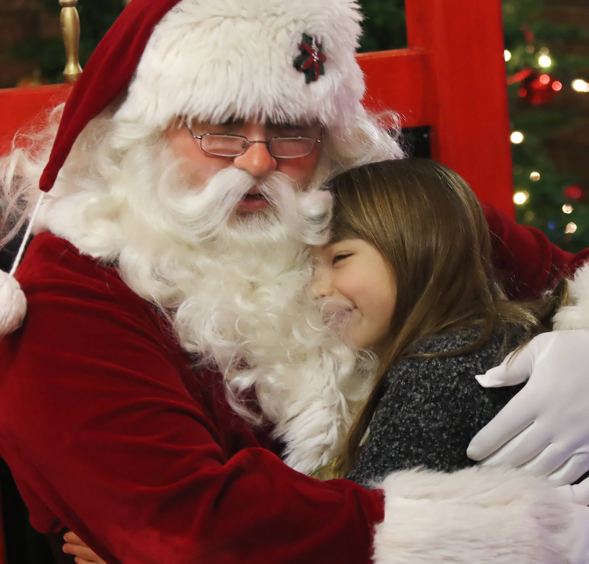 "Ava Yatabe, 8, of Highland Park hugs Santa, played by Robbie Levensbaum, during ""Breakfast With Santa"" at Lambs Farm in Libertyville on Sunday. Families enjoyed brunch as children visited with Santa and made holiday crafts."