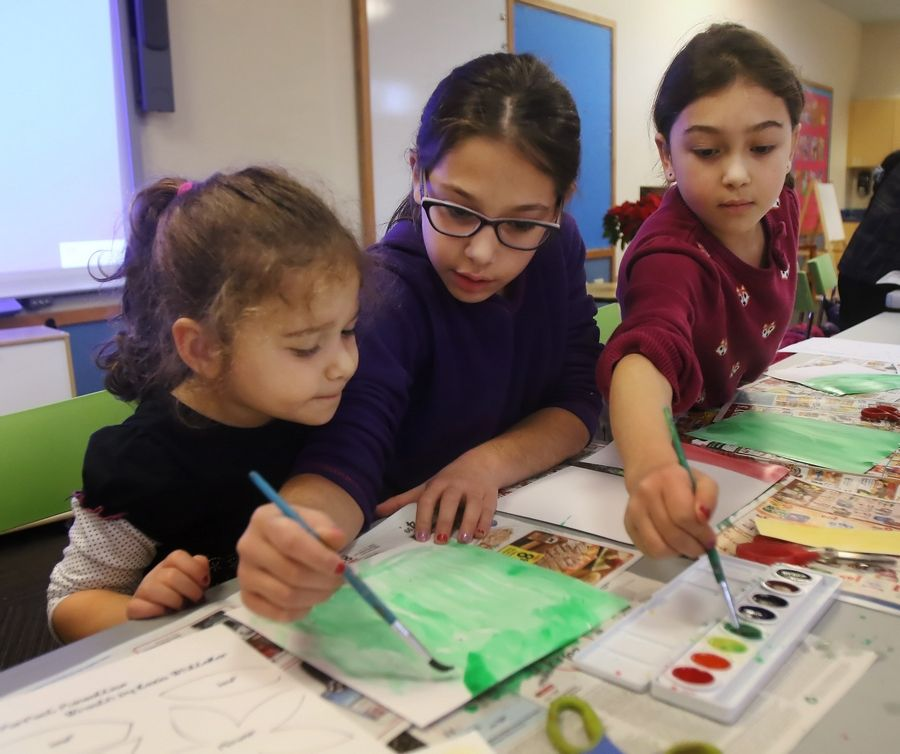 Sisters Suzanna, 3, left, Stella, 10 and Sofia Pashyan, 8, of Hawthorn Woods use watercolor to paint poinsettias during the Viva! Mexico program Monday at Ela Area Public Library in Lake Zurich. The event featured stories about Mexico and an art project based on poinsettias.