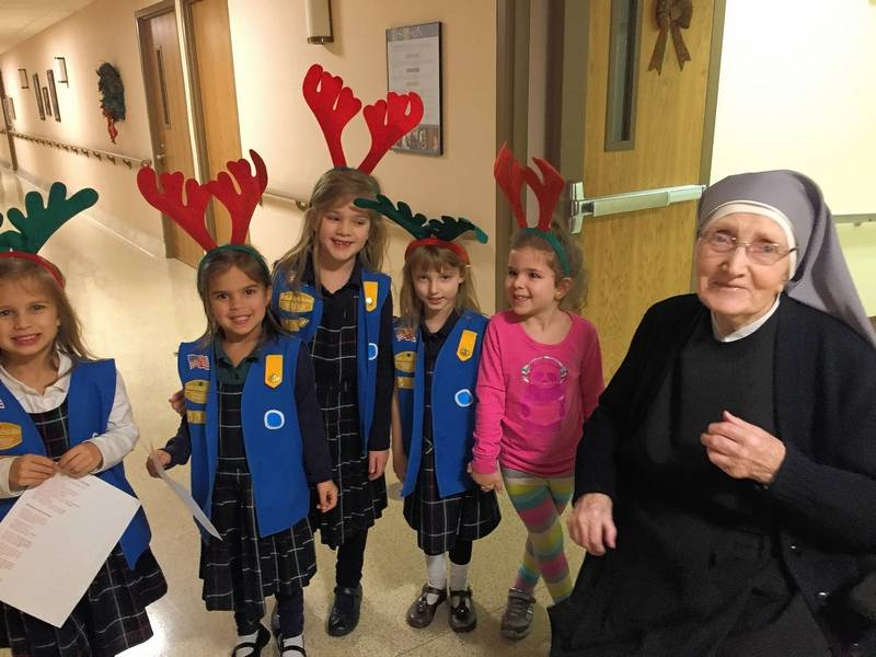 Wearing reindeer antlers, Daisy Girl Scouts from St. Theresa School in Palatine visit with