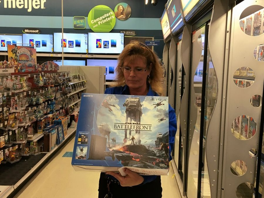 One of Santa's elves, Meijer employee LeAnne Clayton, carries the PlayStation 4 game system she has pulled from the shelves at the store in Elgin after a boy at Alexian Brothers Women & Children's Hospital made a Christmas wish to Santa via a FaceTime conversation.