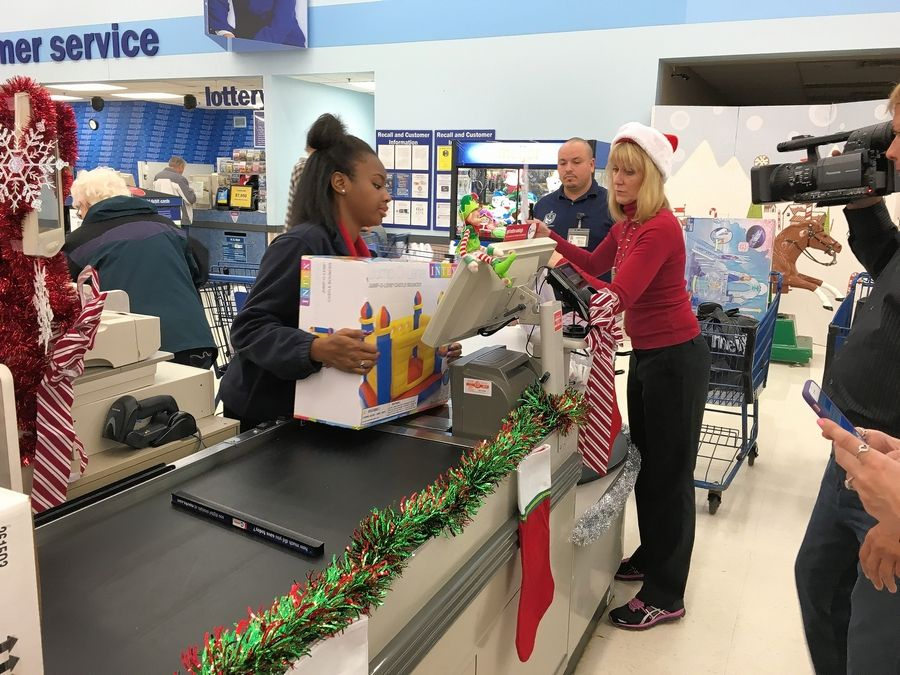 Meijer employee Iesha Childs runs gifts pulled from the shelves of the store in Elgin through the checkout. They were then wrapped and delivered to children at Amita Alexian Brothers Women & Children's Hospital in Hoffman Estates.