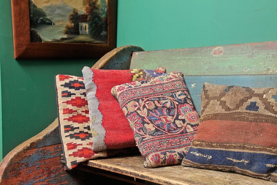 Antique rugs can find a new life as a pillow, which is becoming a popular way to repurpose and display the antique textiles. Their prices varies widely (these were purchased for less than $25 each) and they are among the  hottest collectibles in the market recently.