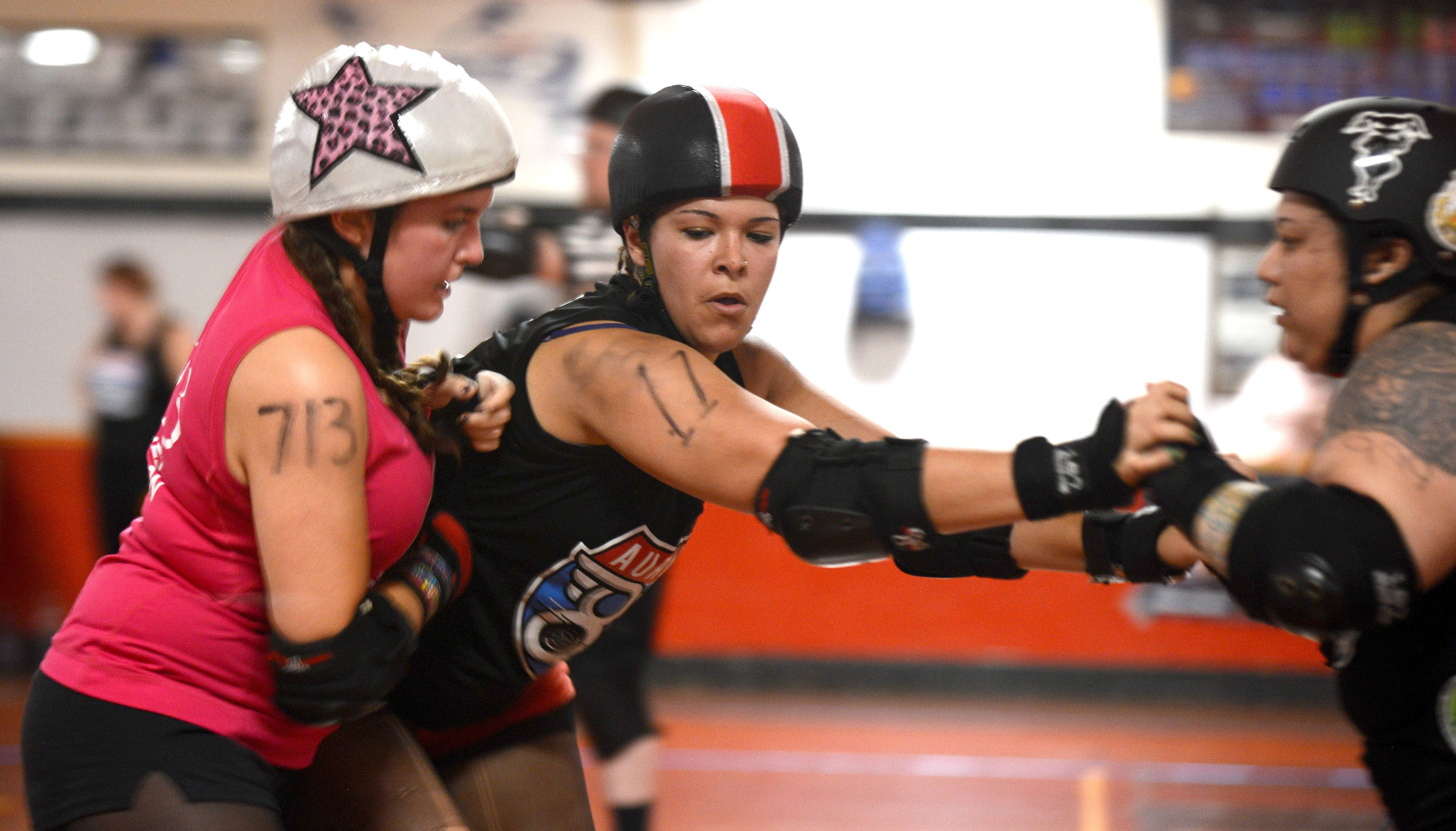 In the pivot position, Charity Hayes of Algonquin, center, works with a teammate to block a jammer from the Cedar Rapids Roller Girls from scoring a point.