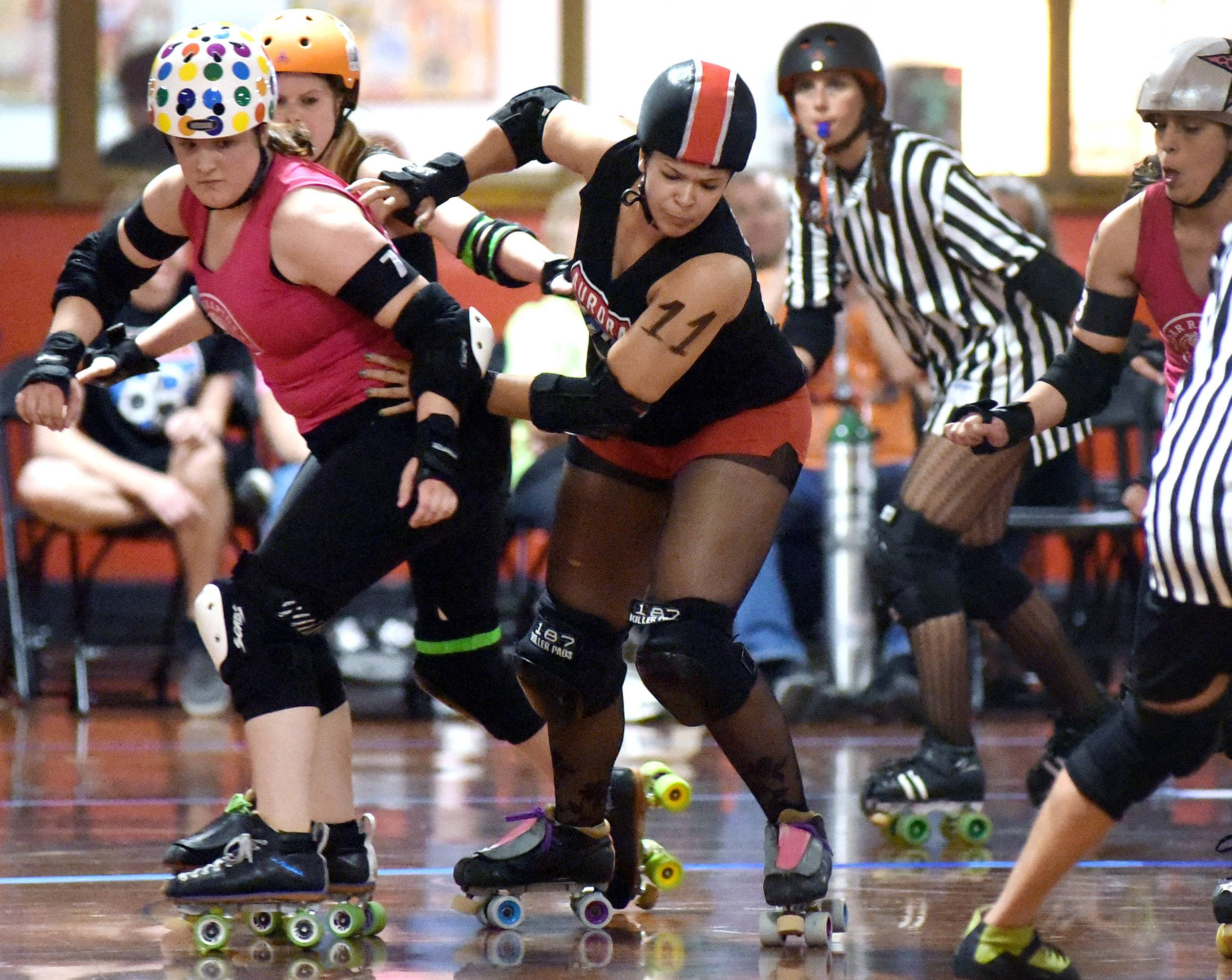 Charity Hayes of Algonquin plays the pivot position and steps in an attempt to stop the jammer from the Cedar Rapids Roller Girls from breaking through and scoring a point over the Aurora 88s.