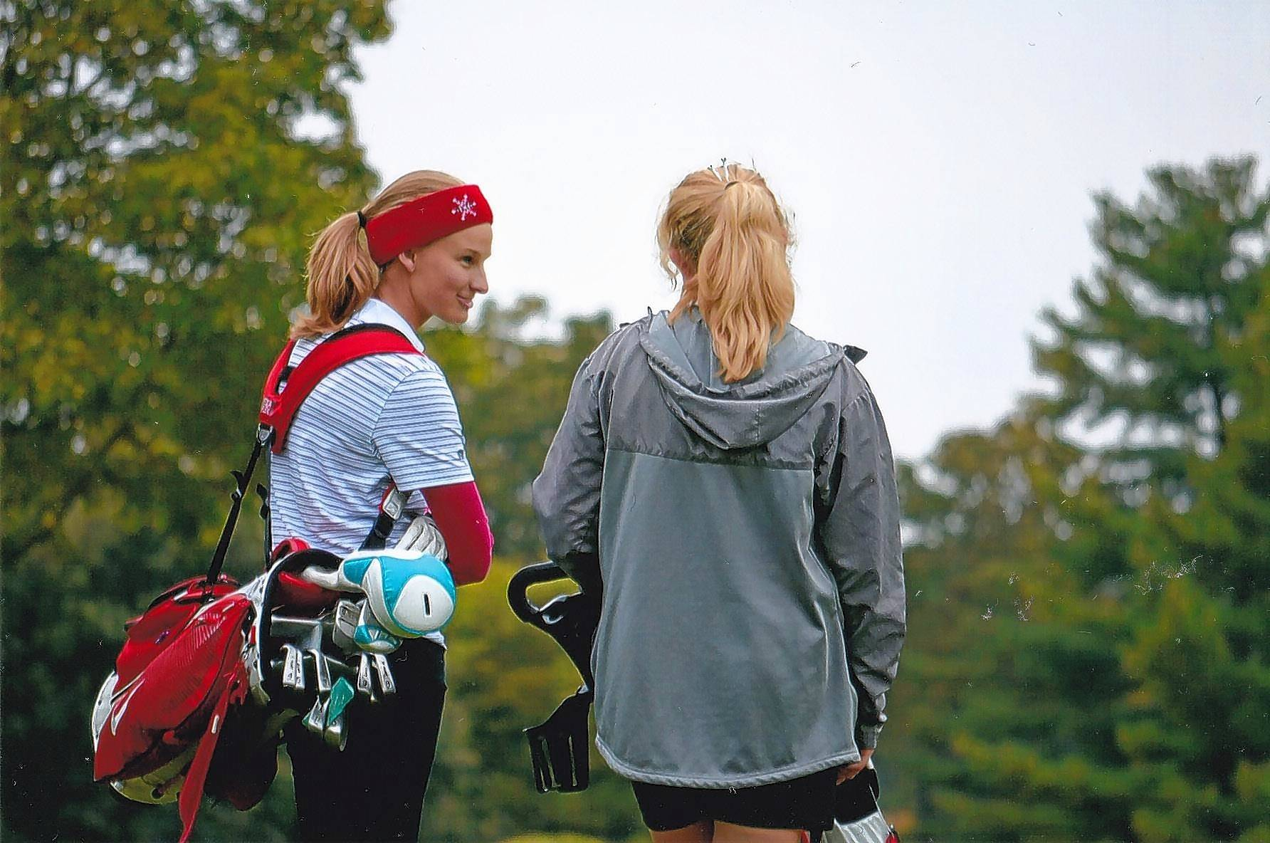 Hannah Gillespie, in red, helps a teammate on the Marian Central Catholic High School golf team. When she began caddying in seventh grade, she knew nothing about golf. She will attend the University of Notre Dame in the fall as an Evans Scholar.
