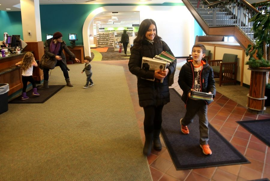 Glen Ellyn mom Mimi Cunningham and her son, Joey, 7, leave the reopened youth department with stacks of books.