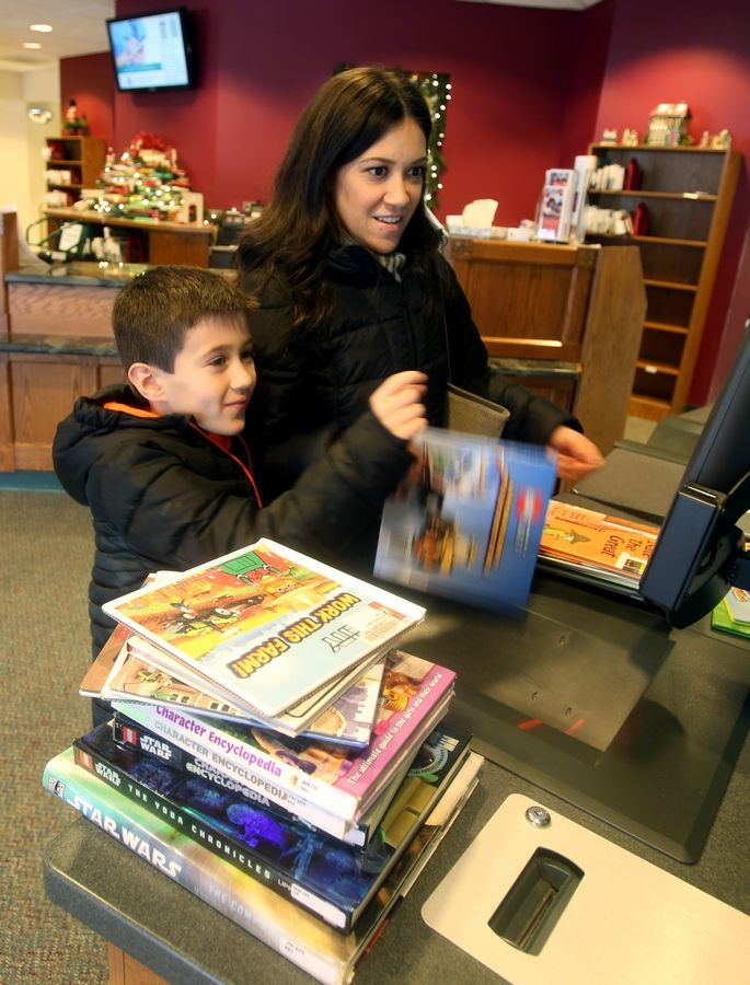 Mimi Cunningham and her 7-year-old son, Joey, check out titles from the youth department of the Glen Ellyn Public Library.