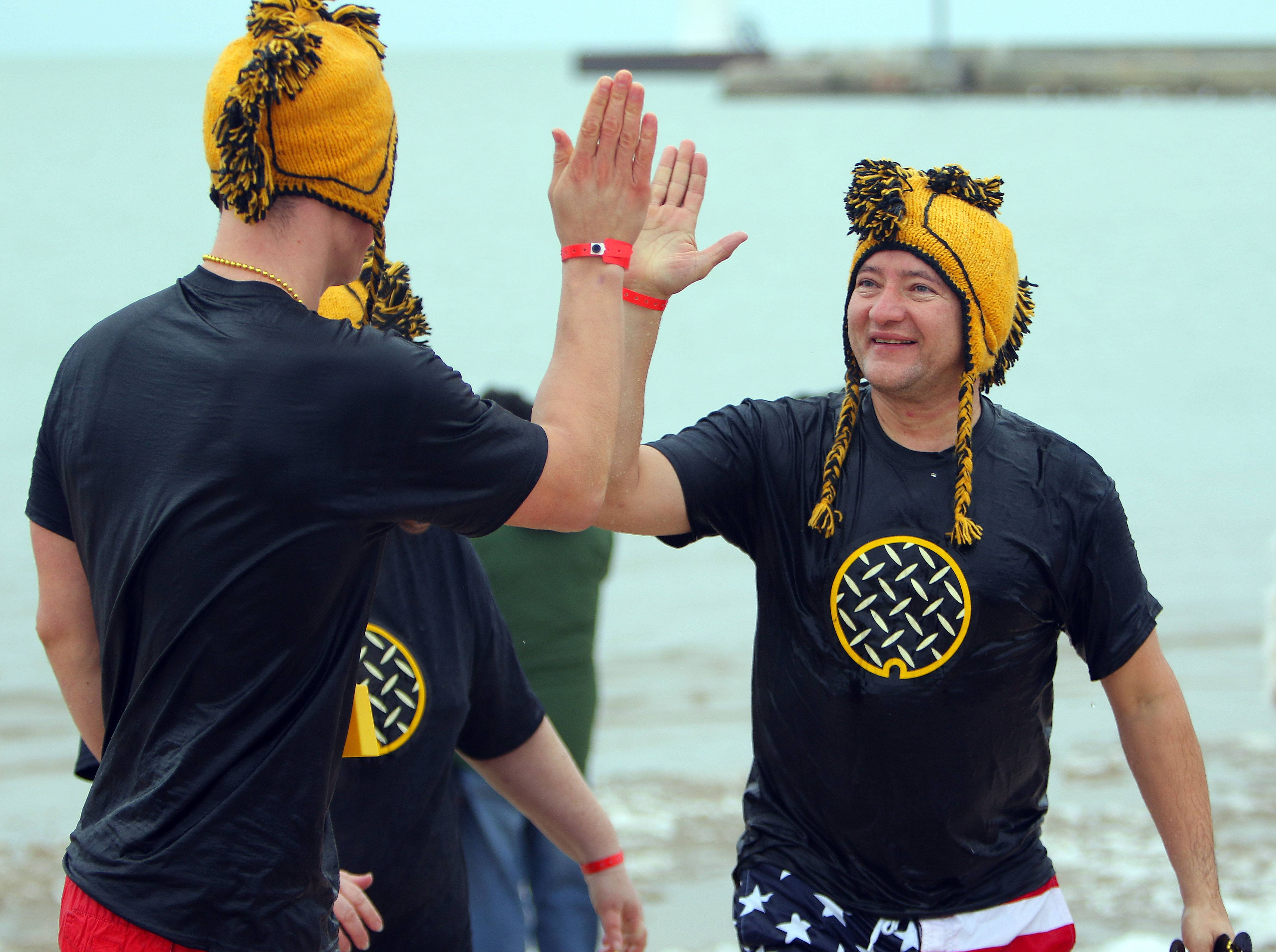 Zachary Wenner, left, and Felix Monterrosa, both of Highwood, high-five after participating in the 17th Annual Polar Bear Plunge Friday in Waukegan.