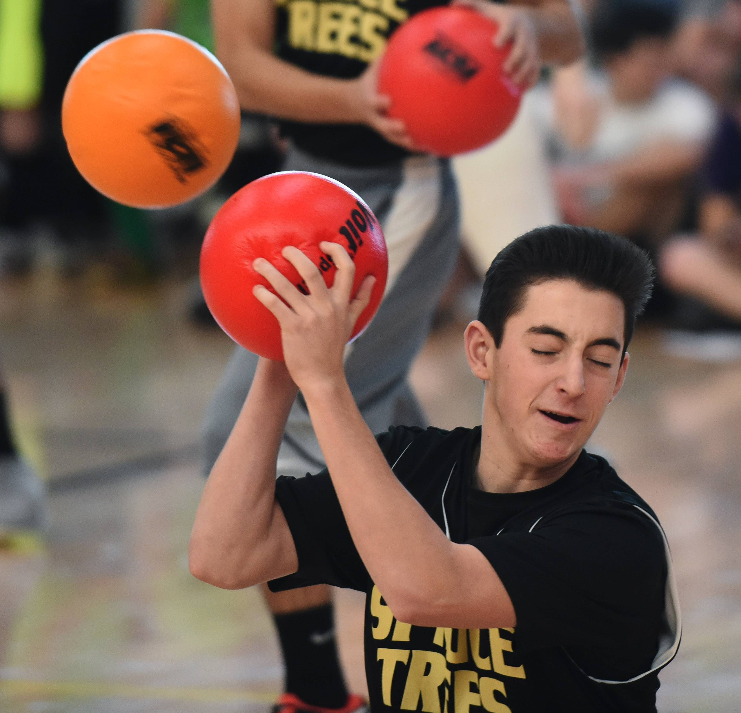 "Pat Burchfield of Roselle, a Conant High School sophomore and a member of the ""Spruce Trees"" team, deflects a ball during the Winter National Dodgeball Championships at the Schaumburg Park District Sport Center Saturday."