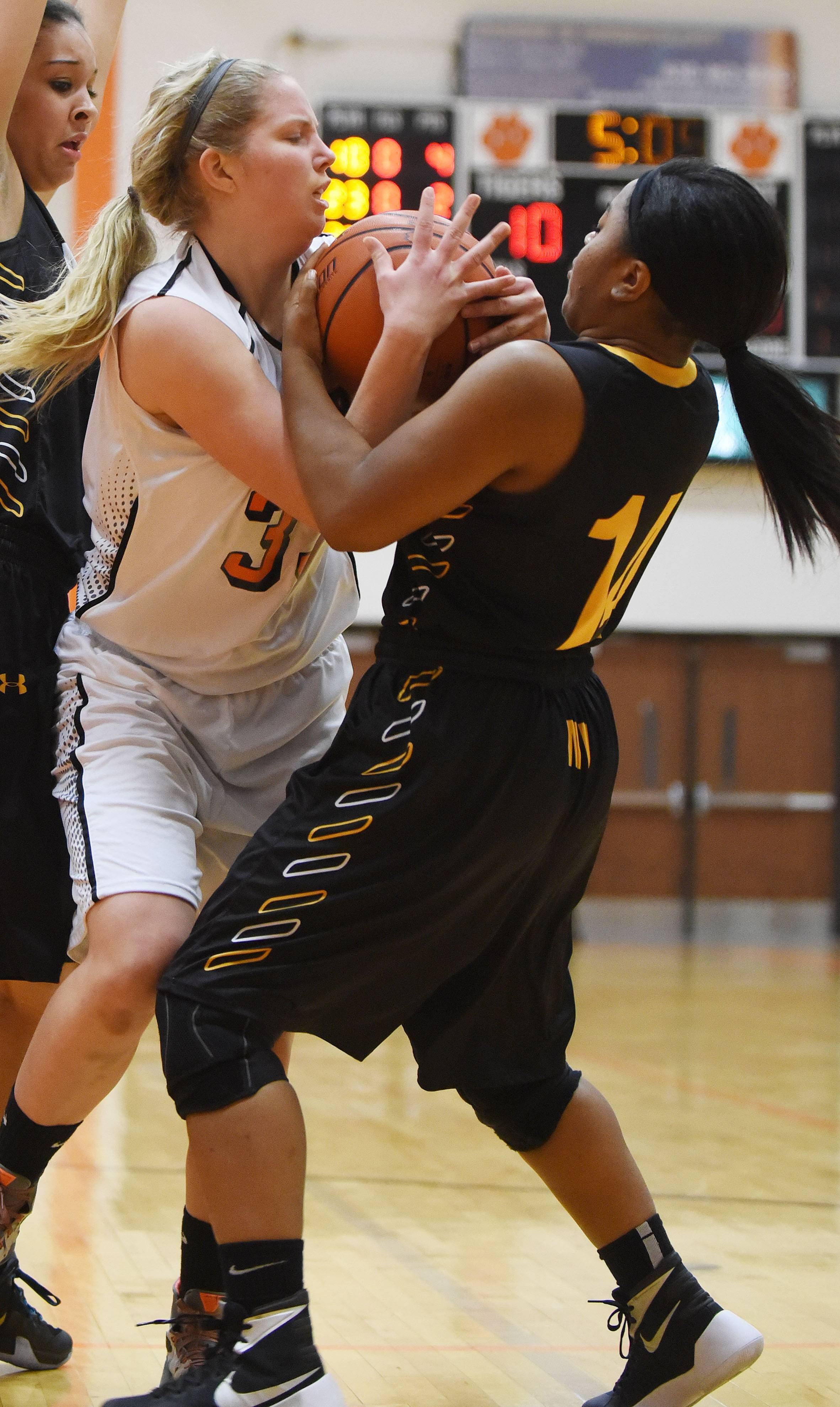 Ellen Anderson of Wheaton Warrenville South and Meryl Barns of Metea Valley vie for control of the ball.