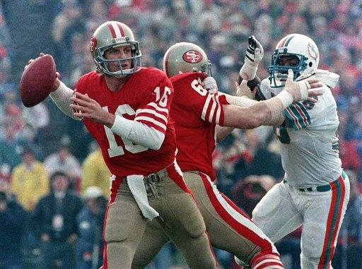 FILE - In this Jan. 20, 1985, file photo, San Francisco 49ers quarterback Joe Montana (16) looks for a receiver behind protective blocking of left guard John Ayers (68) against Miami Dolphins' Don McNeal during the first half of NFL football's Super Bowl XIX in Palo Alto, Calif. Montana completed 24 of 35 passes and threw for a Super Bowl record 331 yards and three touchdowns.