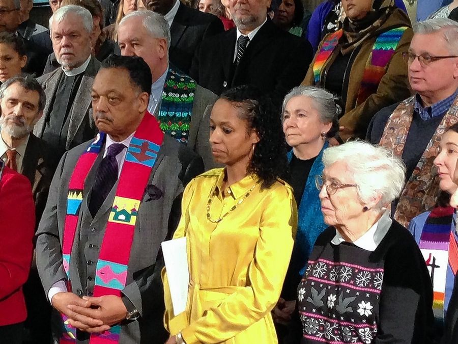 Wheaton College Professor Larycia Hawkins, in yellow, stands next to the Rev. Jesse Jackson Wednesday morning as she prepares to speak in Chicago.
