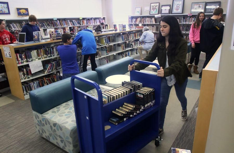 Fremont Middle School eighth-grader Lilly Port pushes a cart of books in the Mundelein school's media center as students reorganize 9,000 books as part of a student project to implement a new cataloging system called C.G.A. DEN based on organizing by color, genre and author. It replaces the Dewey Decimal System.