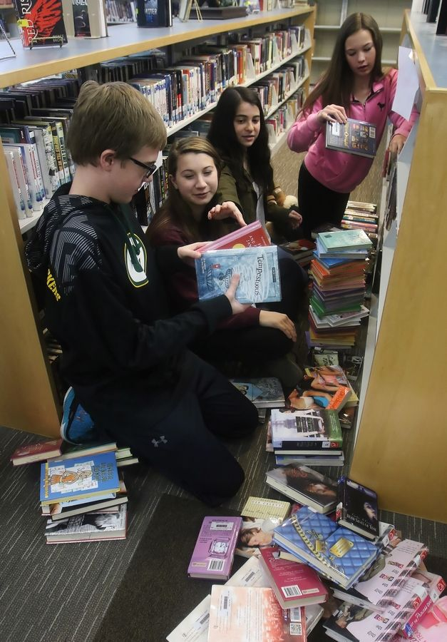 Fremont Middle School eighth-graders Matt Fritz, left, Alexis Naddy, Lilly Port, and Alex Winters pull books from the shelf as part of a student project to reorganize 9,000 books in the media center. The winning plan replaces the Dewey Decimal System with a new cataloging system called C.G.A. DEN based on organizing by color, genre and author.