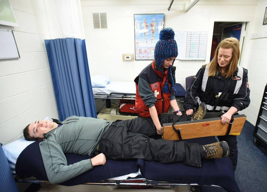 Beginning in the spring, Four Lakes Ski Patrol volunteers learn to handle medical emergencies they might face on the Lisle hill. Patrol member Kevin Yndestad of Naperville plays an injured skier as Kelly Houston, left, of Naperville, and Kadee Korabik of Homer Glen practice work on their leg-splinting skills.