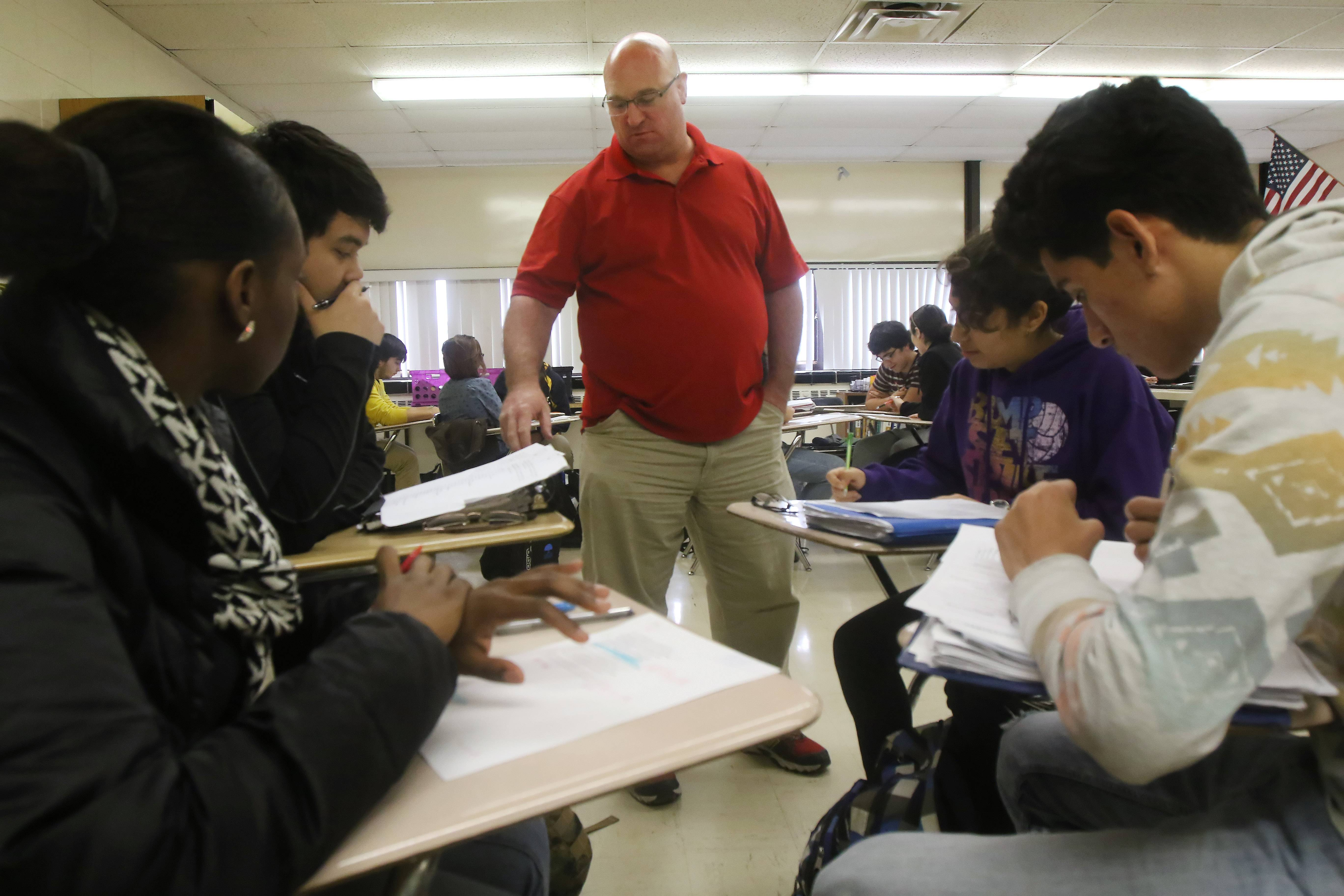 Teacher Bob Diedrich works with students on a paper about Shakespeare sonnets as he teaches an Advanced Placement literature class at Round Lake High School.