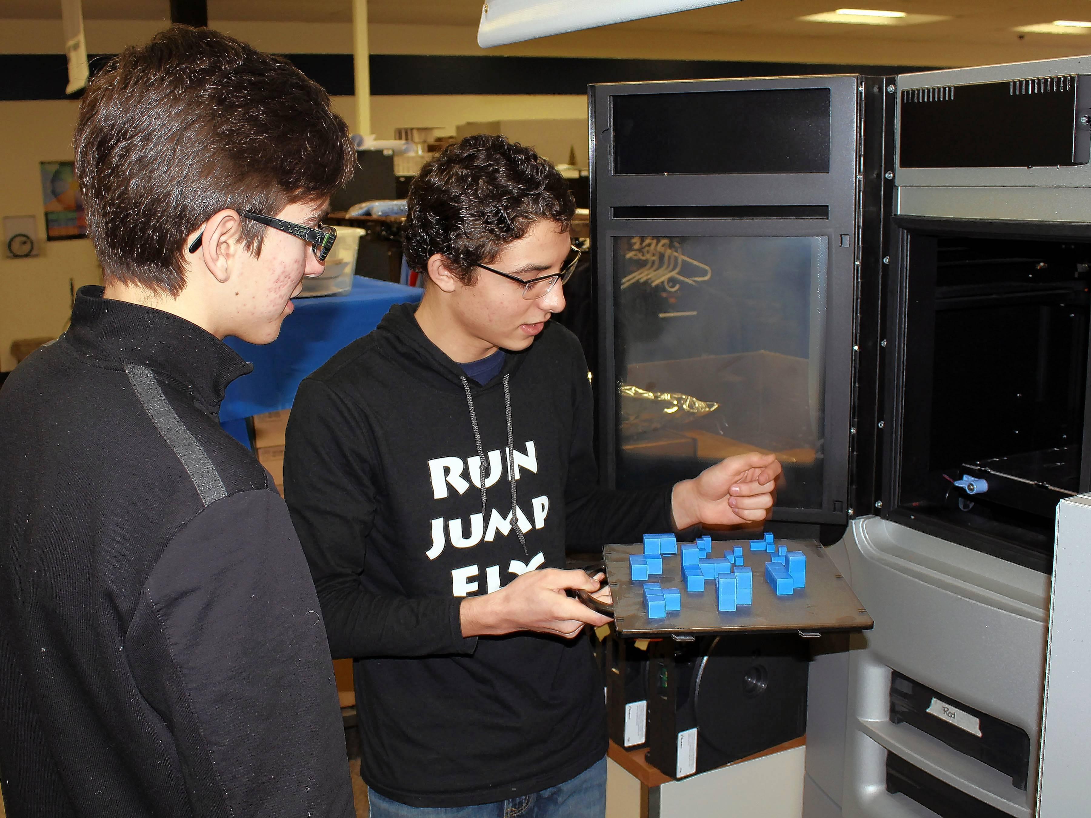 Ben Cavanaugh of Wheaton Warrenville South, from left, and Usama Humecki of Wheaton North used Technology Center of DuPage's 3-D printer to form the final pieces of a puzzle cube design. The printer is used in class to produce prototypes of student designs.