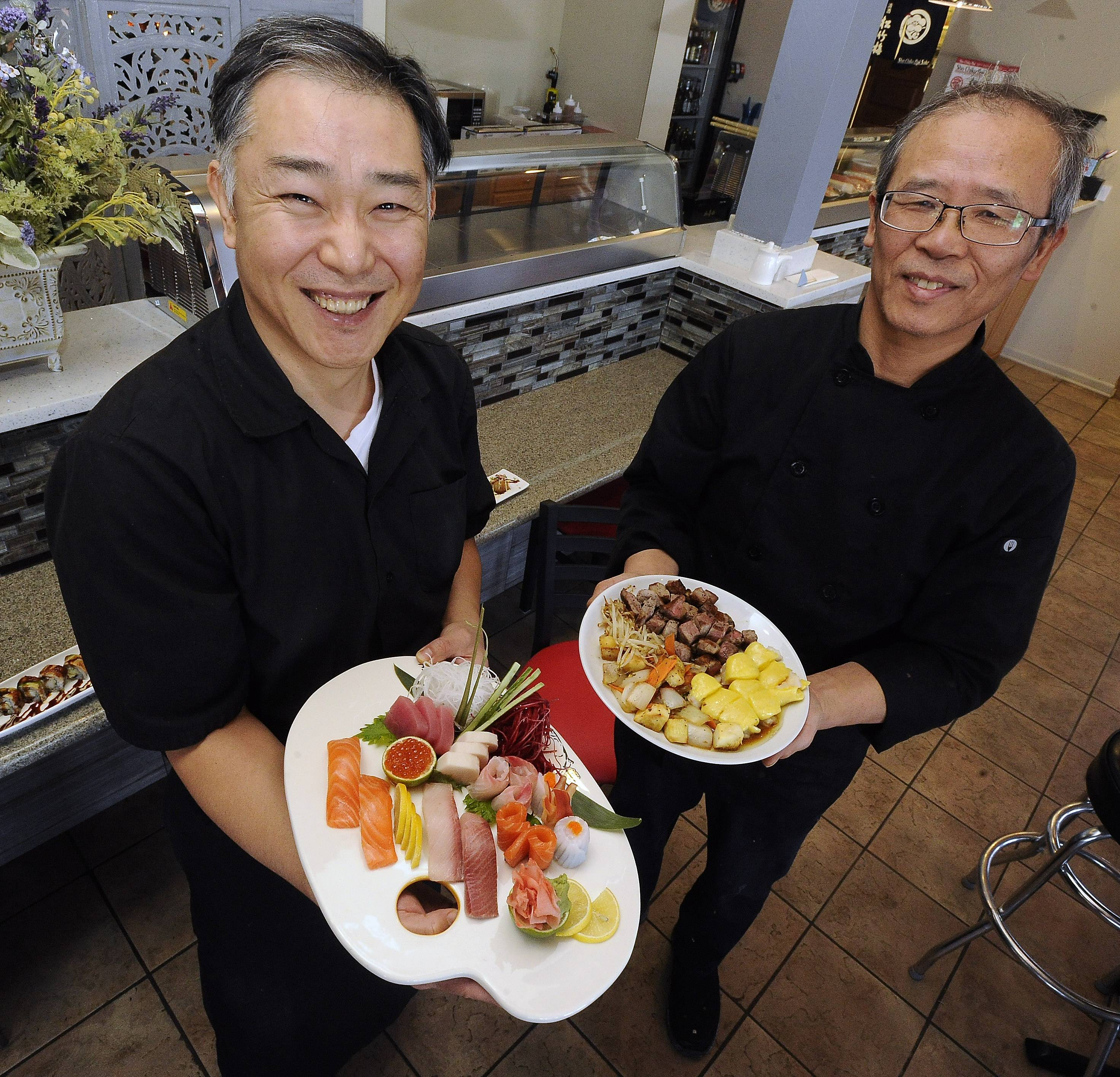 Sushi chef Sang Lee, left, presents the sushi sashimi platter and owner Tony Yi shows off the filet mignon and golden shrimp dish at Ai Hana in Lake Zurich.
