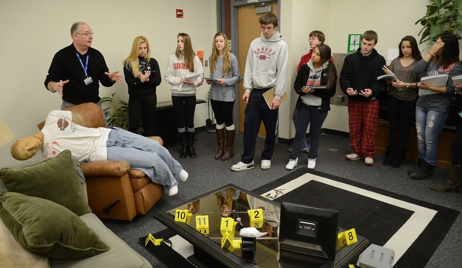 Forensics instructor Mike Smith shows a mock crime scene to dual-credit high school students taking part in a program through Harper College in Palatine to earn 15 college credits before graduating high school. Community Unit District 300 is launching a new program this fall with Elgin Community College allowing a select group of high school seniors the opportunity to take a full year of college courses before they graduate.