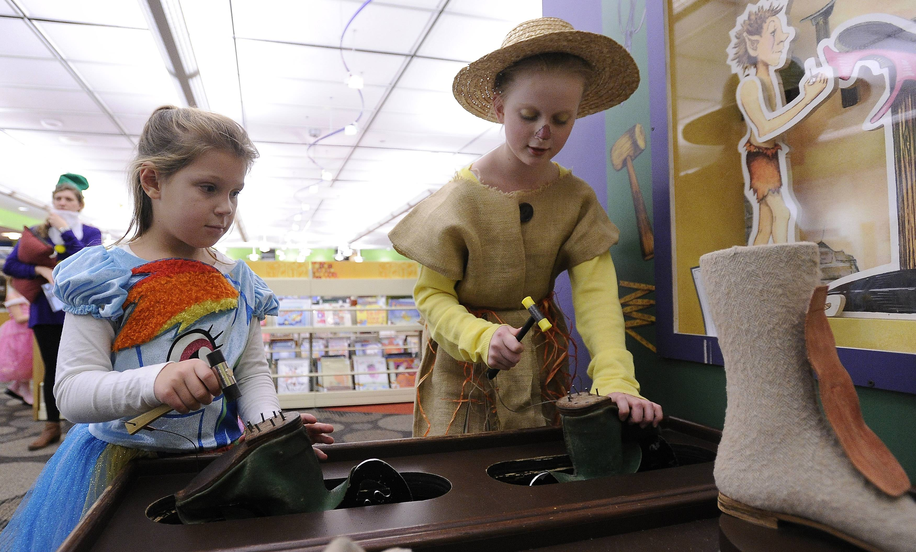 Kamila Starenda, 6, and her sister Amelia, 10, do a bit of hammering on the fairy tale adventures at the Arlington Heights Fairy Tale and Fantasy Gala at the Arlington Heights Memorial Library on Saturday.