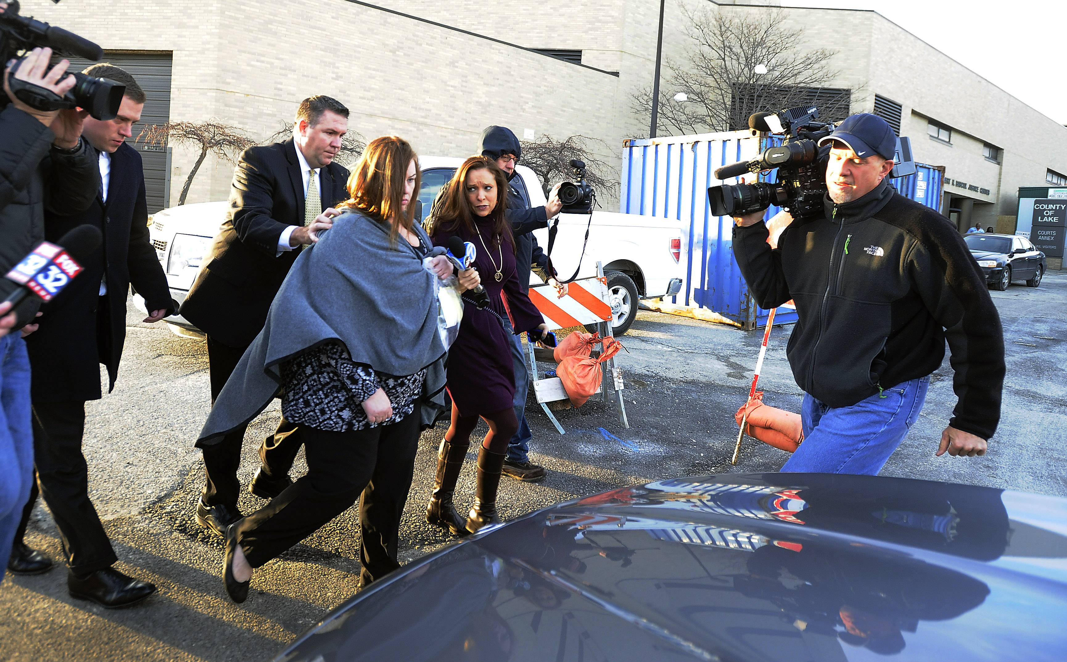 Melodie Gliniewicz is pursued by news reporters as she rushes to her lawyer's car outside the Lake County sheriff's office in Waukegan on Wednesday.