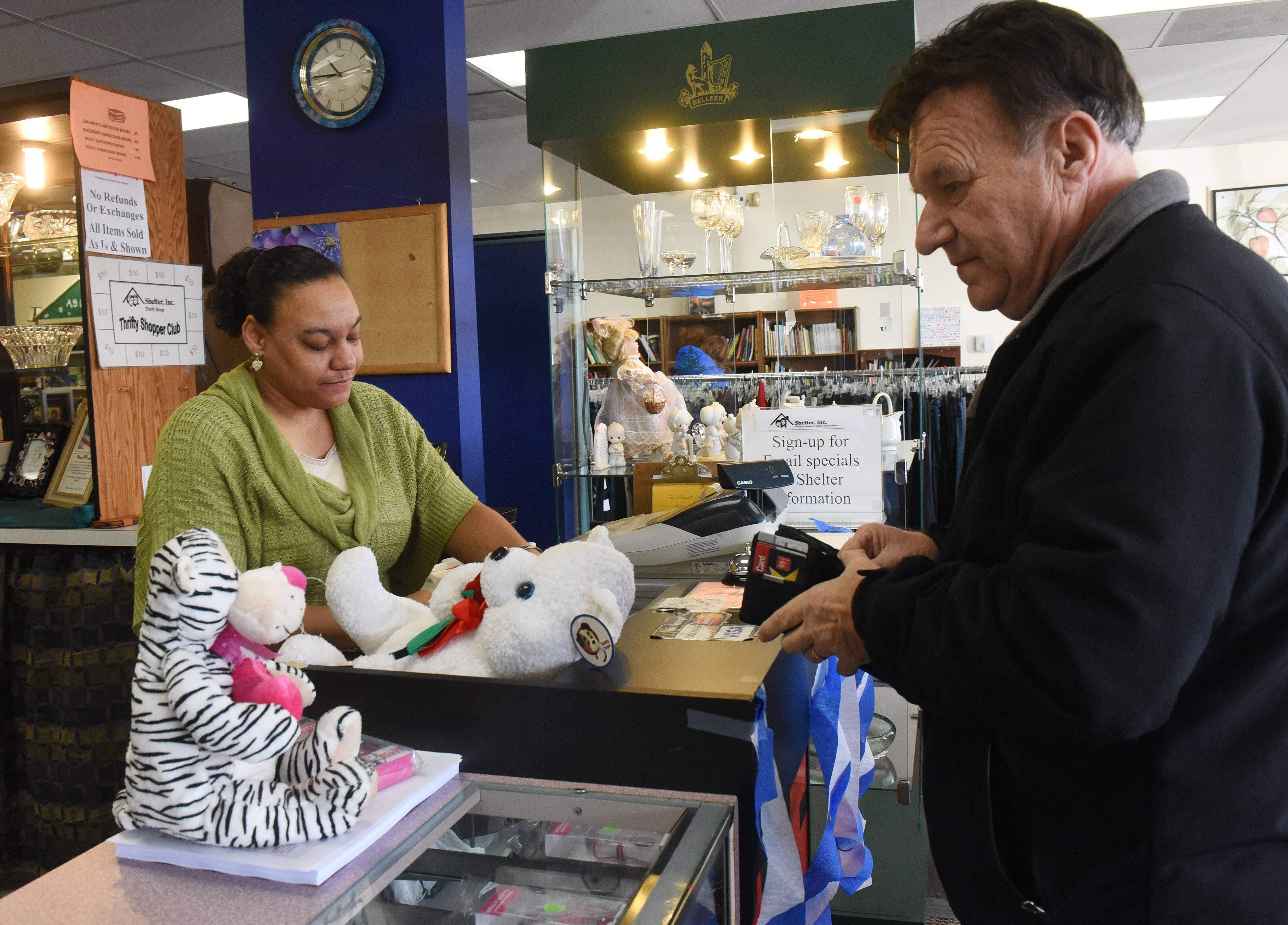 Sales associate Marsha Kwabena totals items being purchased by customer John Gul of Streamwood during the grand reopening of Shelter Inc.'s Schaumburg thrift shop Saturday.