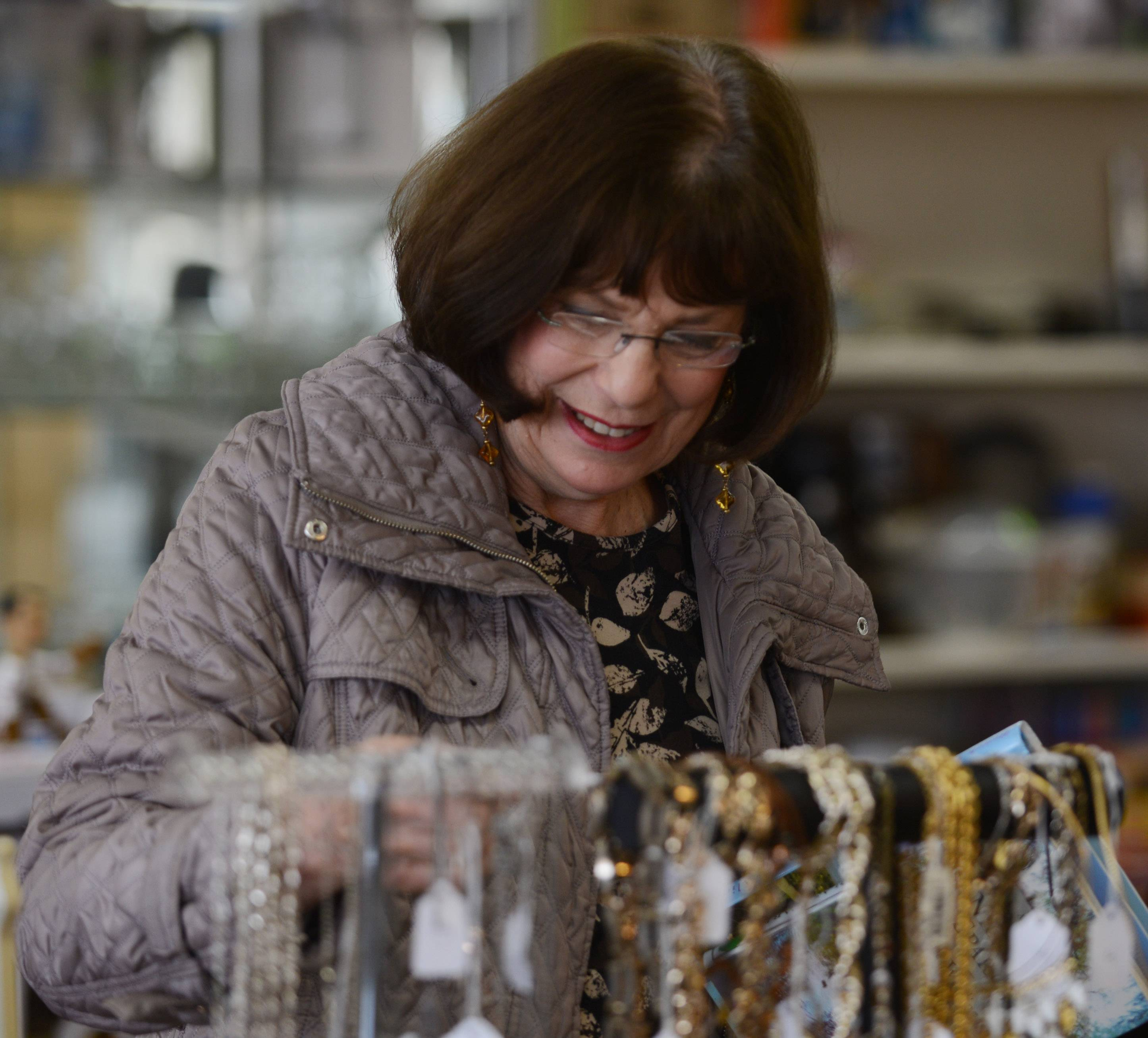 Joanne Kluck of Elk Grove Village views jewelry items during the grand reopening of Shelter, Inc.'s Schaumburg thrift shop Saturday.