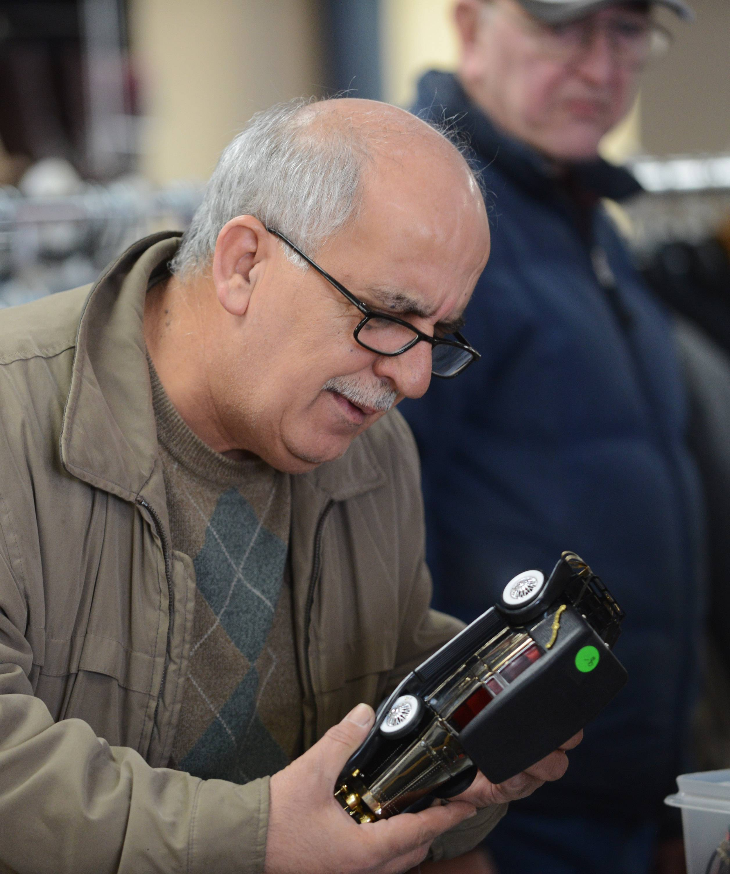 Emmanuel Malik of Schaumburg views a model car while shopping during the grand reopening of Shelter, Inc.'s Schaumburg thrift shop Saturday.