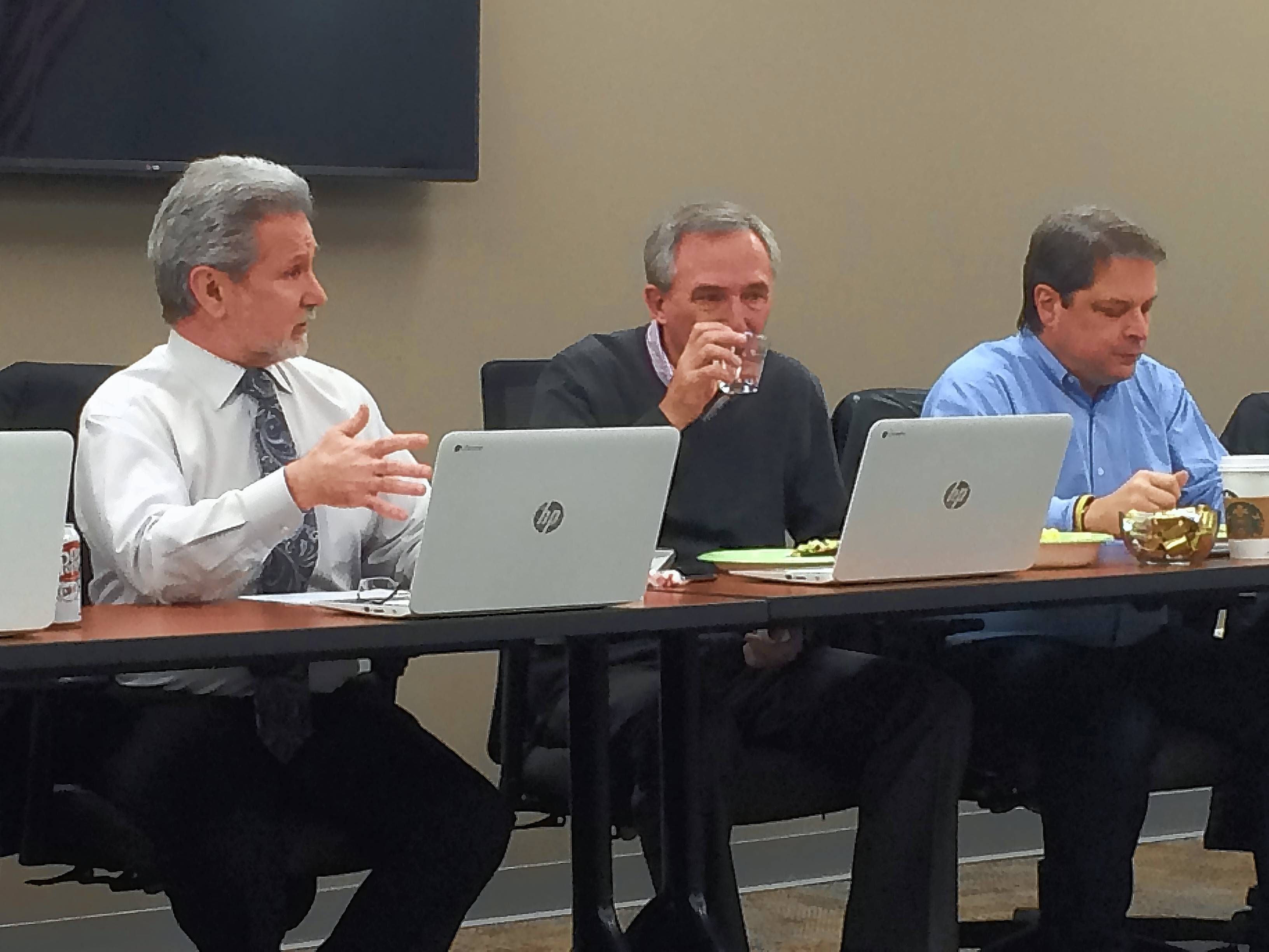 Superintendent Prentiss Lea, left, talks to Libertyville-Vernon Hills Area High School District 128 board members about the district's finances Monday night. Board members Pat Groody and Jim Batson sit to his left.