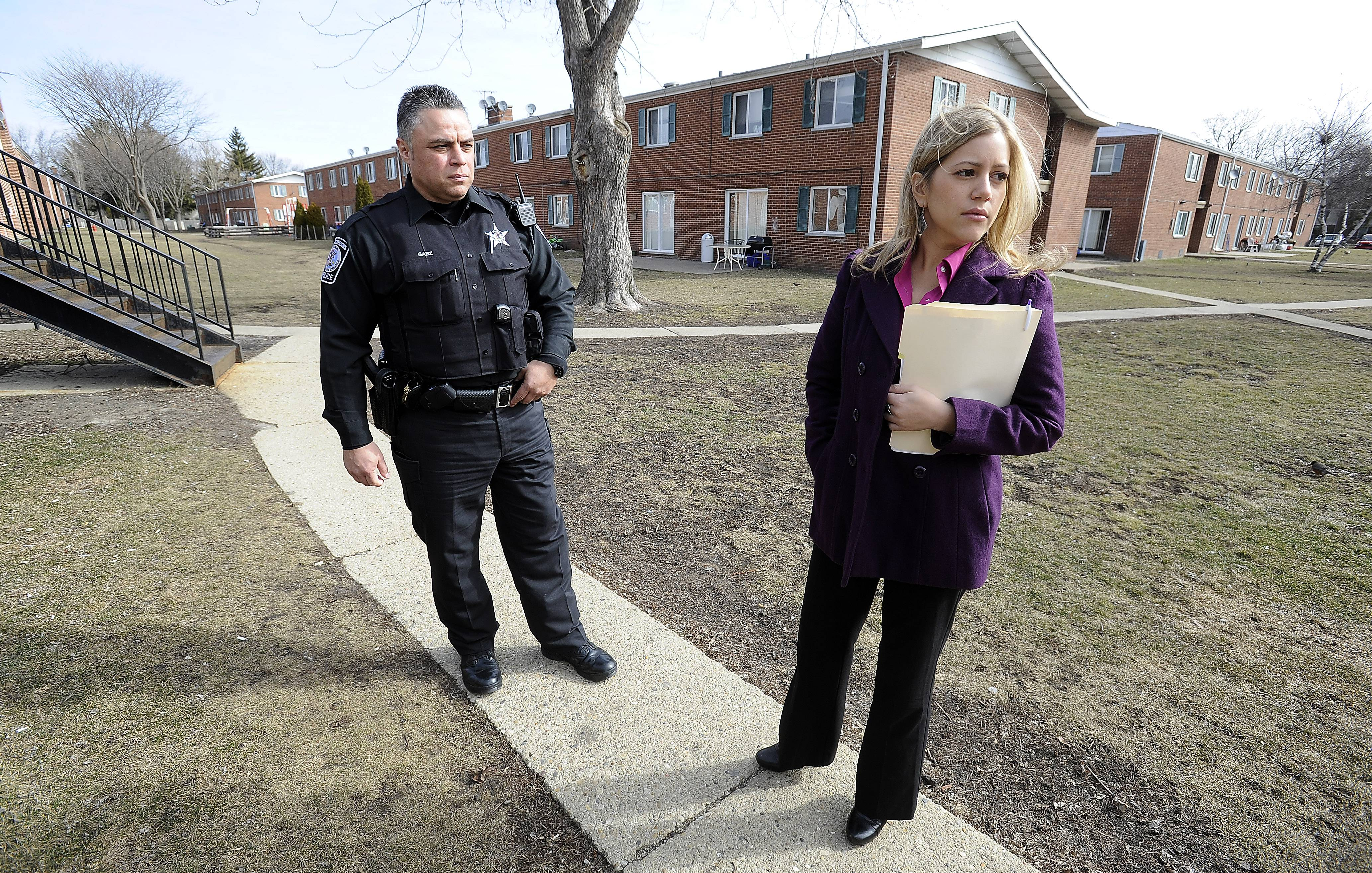 Rolling Meadows police Officer Carlos Saez and police social worker Natalia Mercado walk the grounds at the East Park apartments, providing residents with different services.