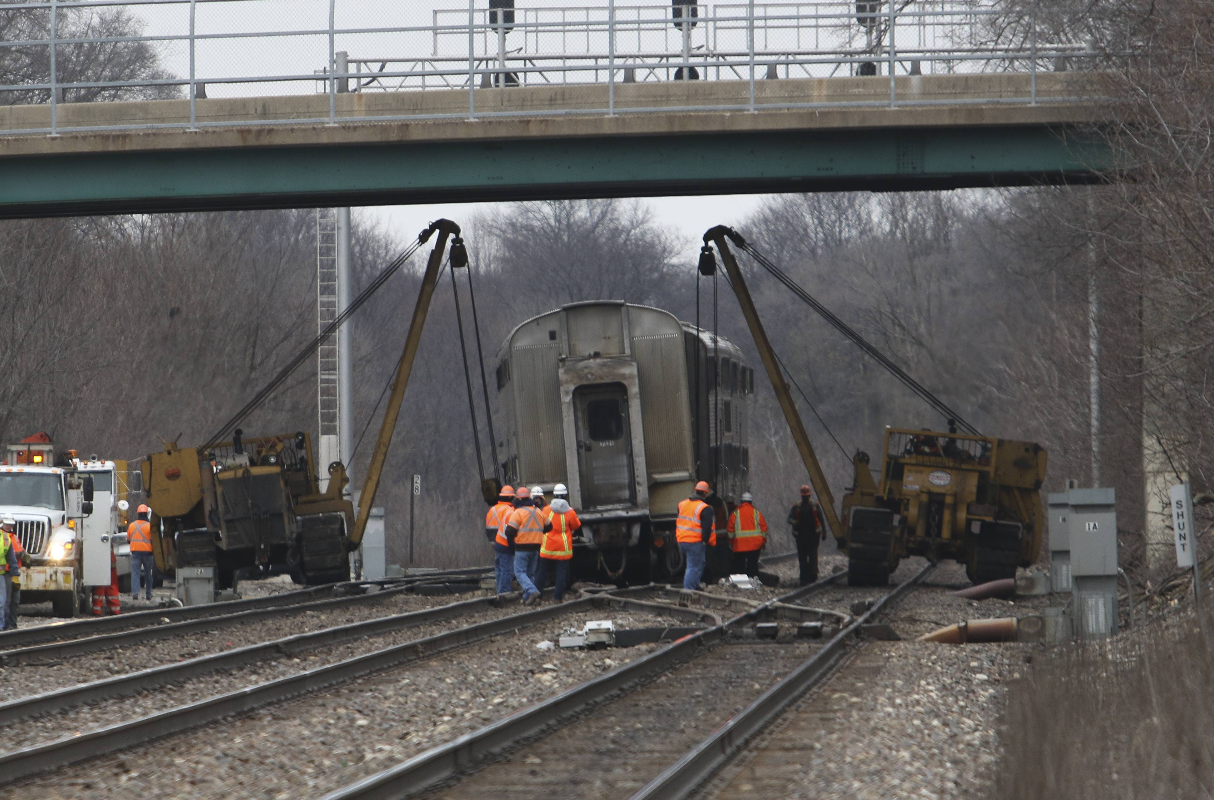 Crews work Monday morning to remove a Metra train that derailed just east of the downtown Naperville train station.