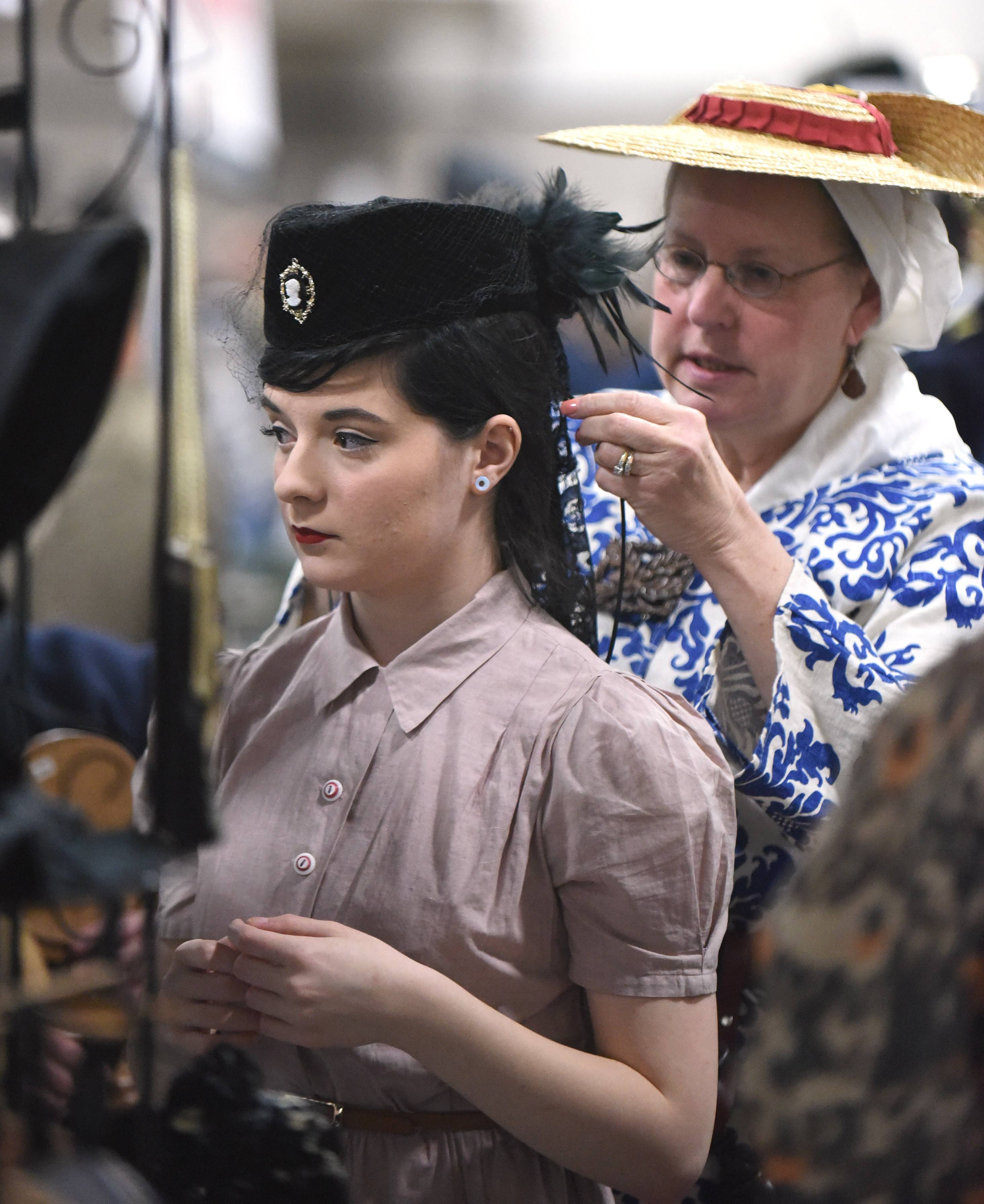 Sam Bellassai, 17, of Frankfort is fitted with a hat for her 1940s era costume by Deborah Kelly of Danville in the Ladies & Gentlemens Emporium vendor booth (out of Oakwood) during Military History Fest at the Pheasant Run Mega Center Saturday. Bellassai has been a re-enactor for three years; Kelly (dressed in a Revolutionary War era costume) 35 years.
