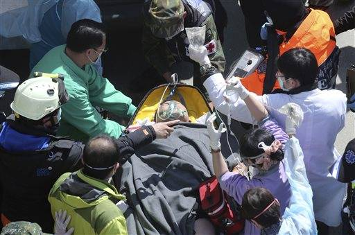 Emergency rescue workers attend survivor Lee Tsung-tien after being rescued from the rubble of a collapsed building complex in Tainan, Taiwan, Monday, Feb. 8, 2016. Two survivors - one found shielded under the body of her husband - were pulled out alive from a toppled high-rise apartment building on Monday, two days after a powerful quake. (AP Photo) TAIWAN OUT
