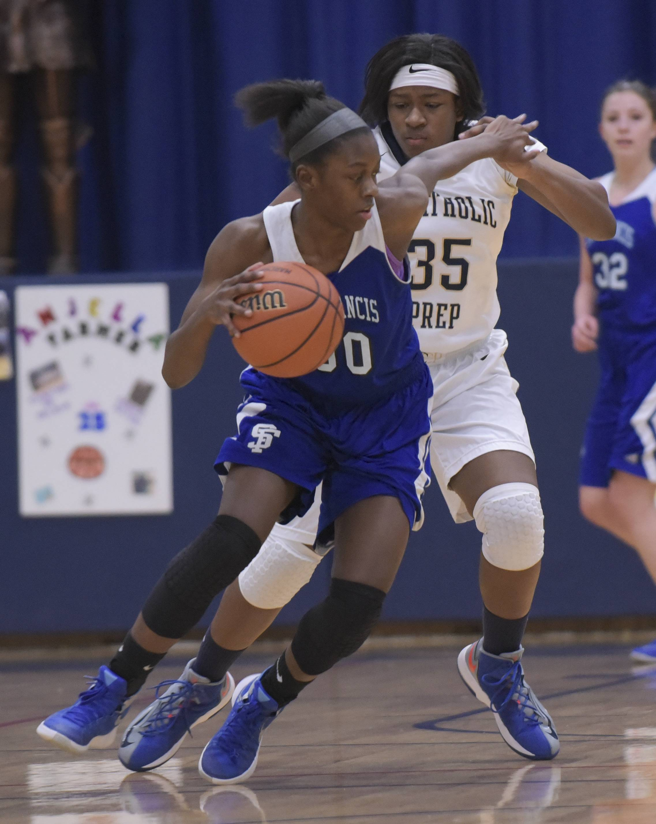 St. Francis' Antwainette Walker moves around I C Catholic Prep's Lillian Brown during varsity girls basketball in Elmhurst Monday.