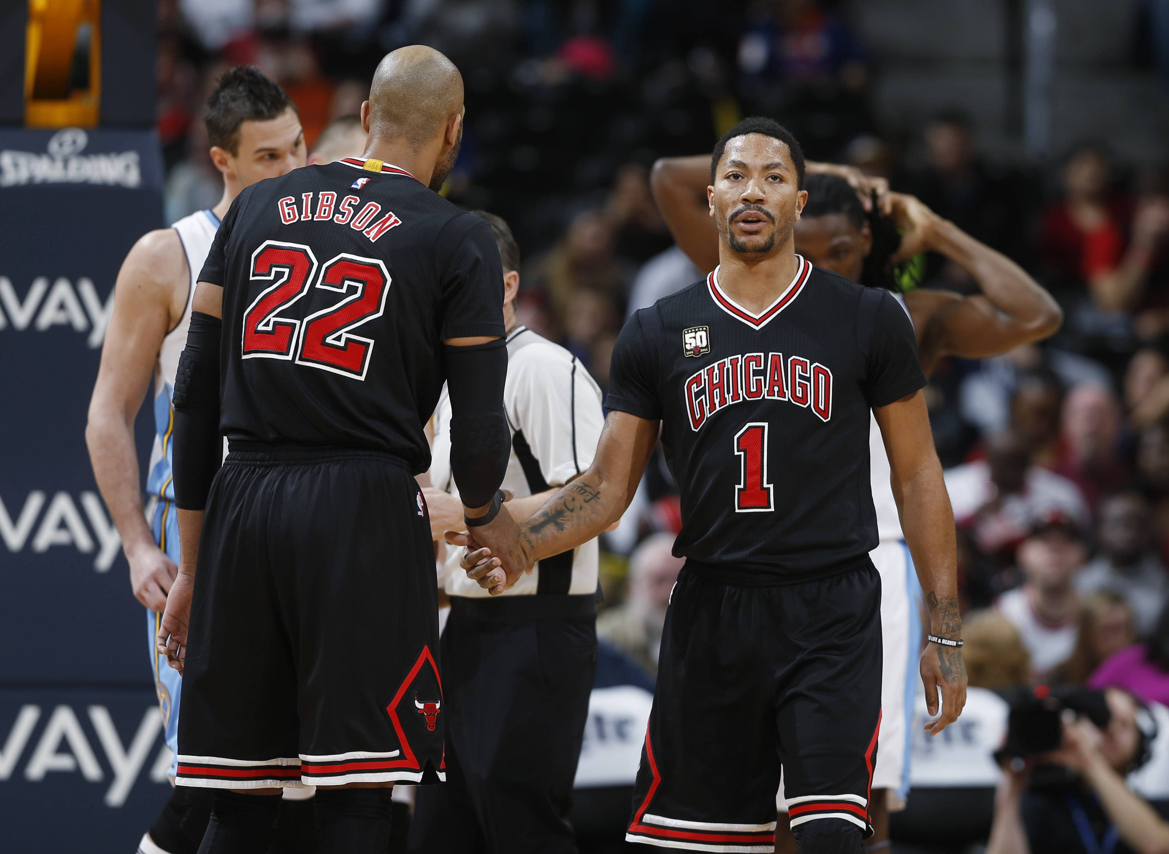 Chicago Bulls guard Derrick Rose, being congratulated by teammated Taj Gibson after making a basket and drawing a foul last Friday night at Denver, sat out Monday night's loss to Charlotte with general body soreness.