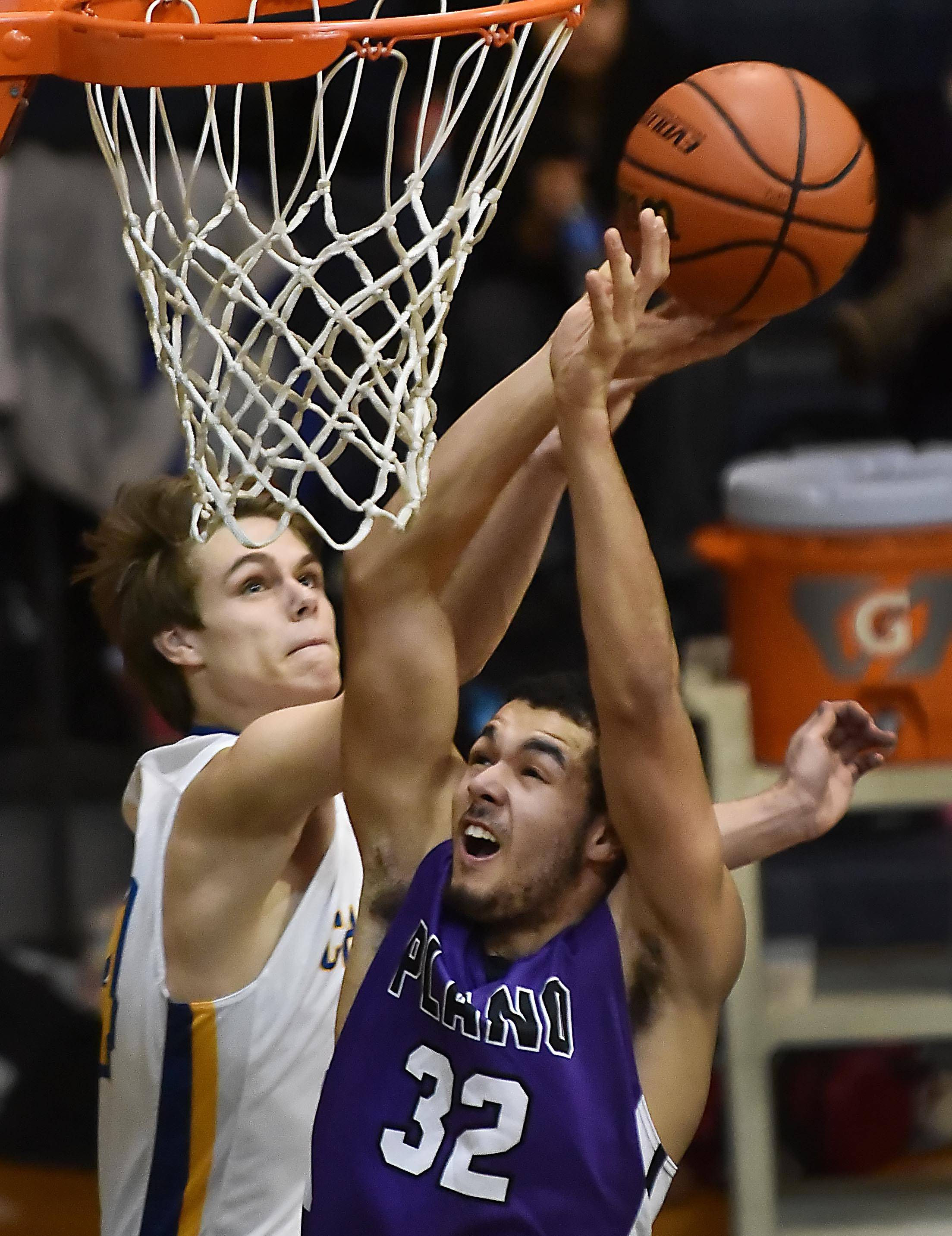 Aurora Central Catholic's Jake Bush blocks a layup by Plano's Marcus McKinney Monday in Aurora.