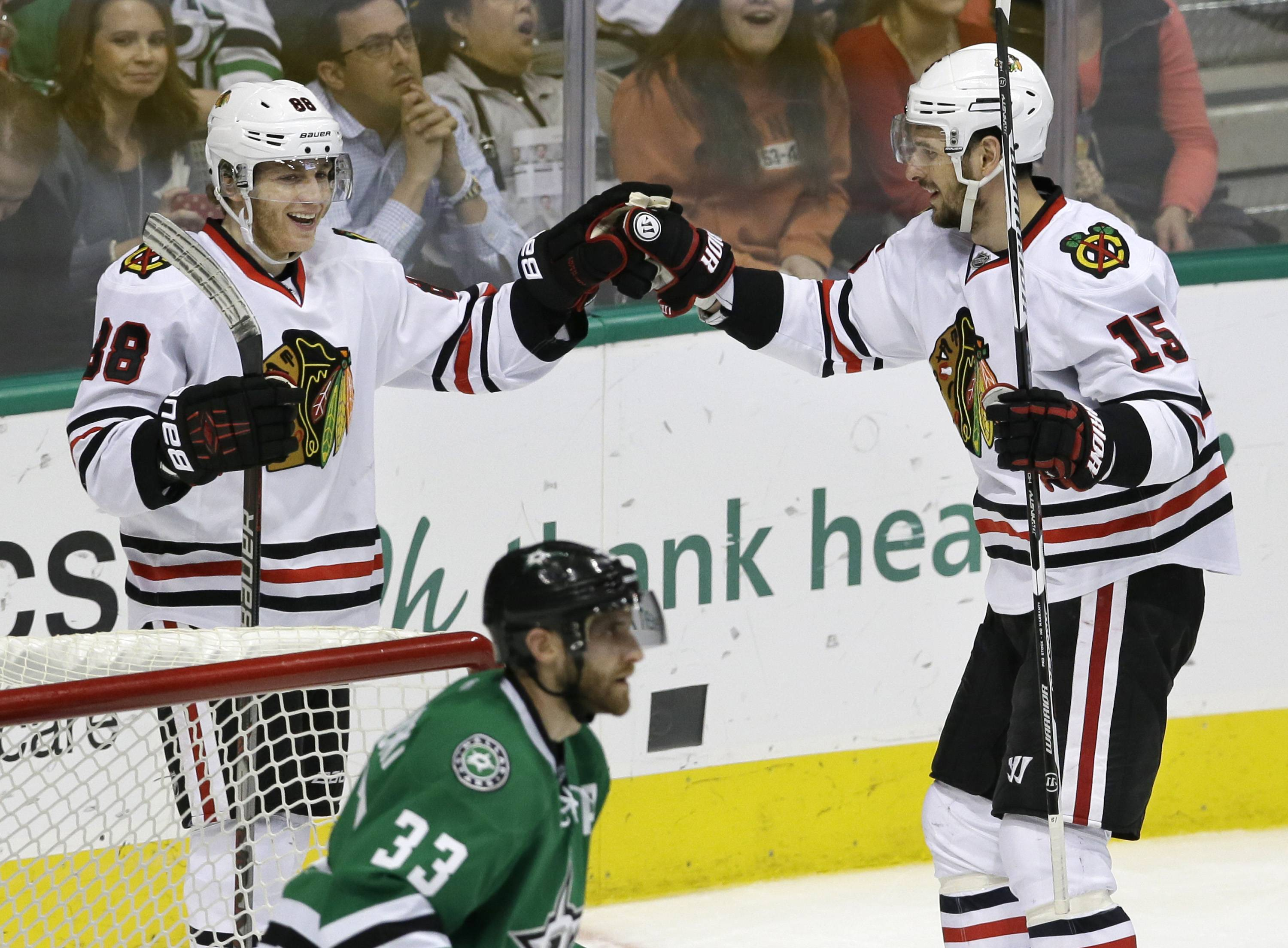 Chicago Blackhawks right wing Patrick Kane (88) celebrates scoring his goal with teammate Chicago Blackhawks center Artem Anisimov (15) as Dallas Stars defenseman Alex Goligoski (33) skates off during the second period of an NHL hockey game Saturday, Feb. 6, 2016, in Dallas. (AP Photo/LM Otero)