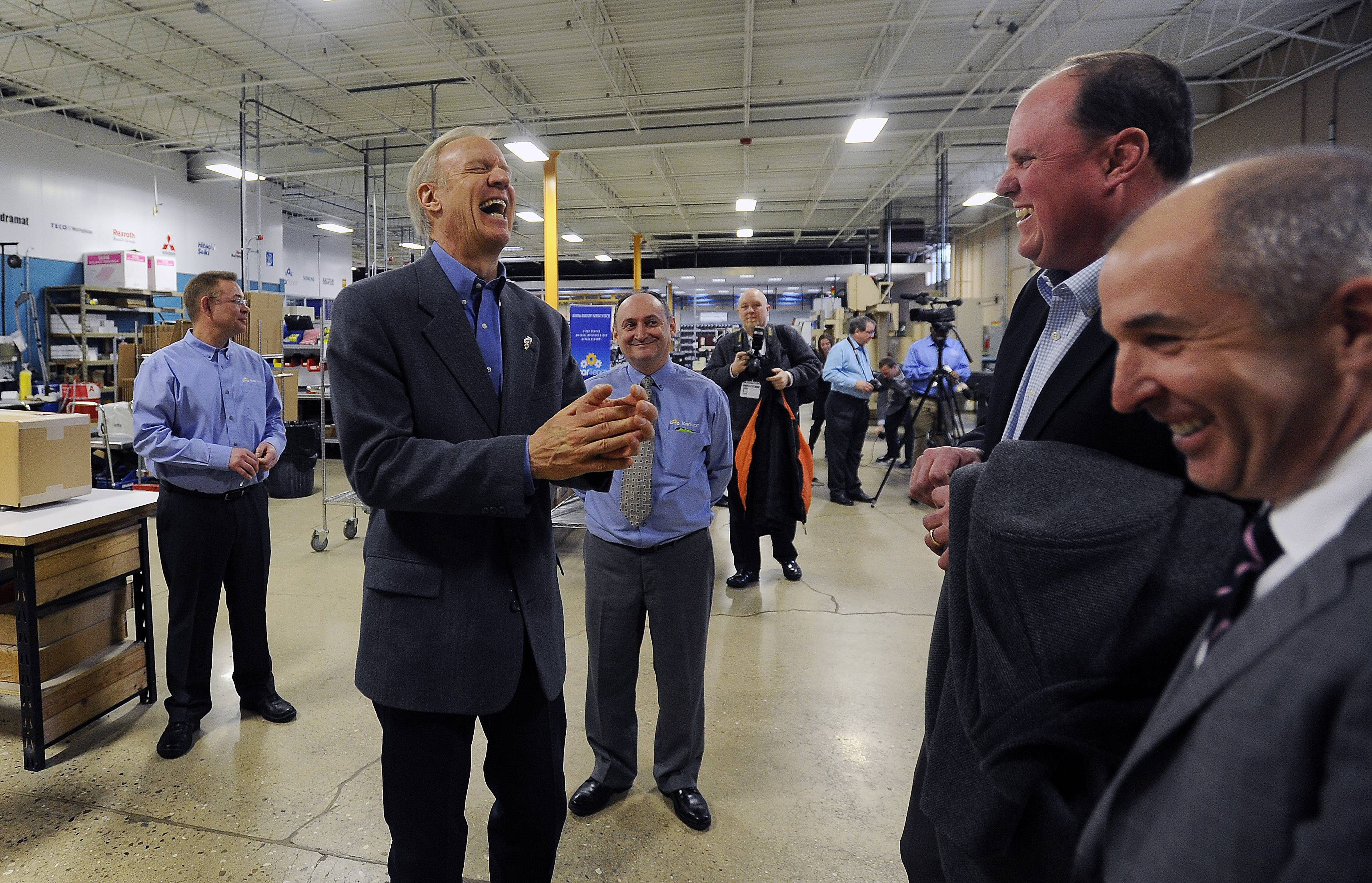 Gov. Bruce Rauner shares a laugh with suburban community and business leaders Monday while touring the IcarTeam facility in Wheeling before answering their questions during a town-hall meeting.